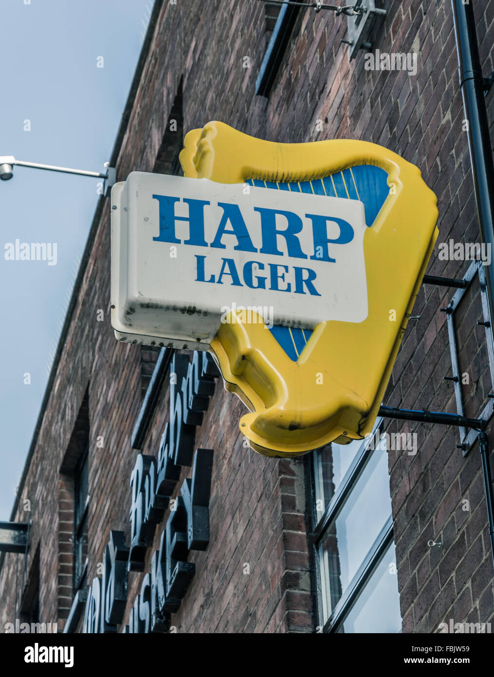 An old Harp Lager beer sign on a Belfast pub. - Stock Image