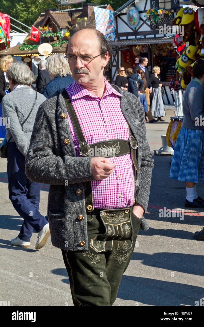 Man in lederhosen strolling at Oktoberfest in Munich, Germany. - Stock Image