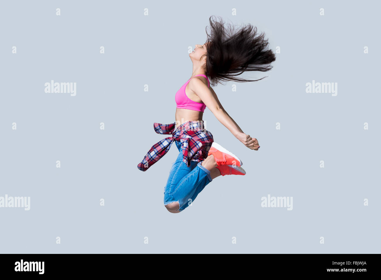Beautiful young happy smiling fit modern hip-hop dancer woman working out wearing jeans, jumping, studio, gray background - Stock Image
