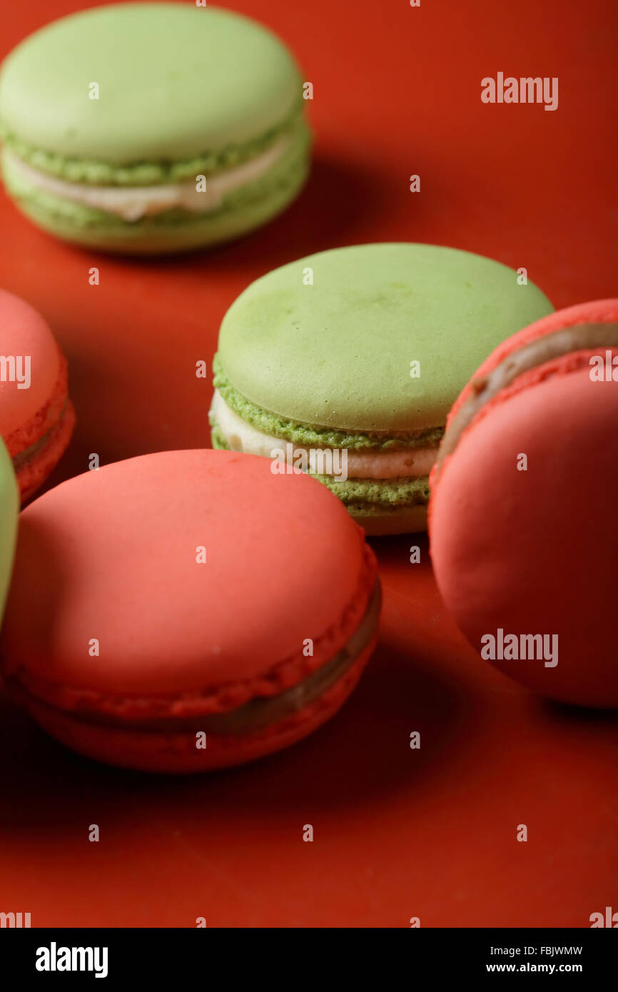 macaroons close-up on red background, french food - Stock Image