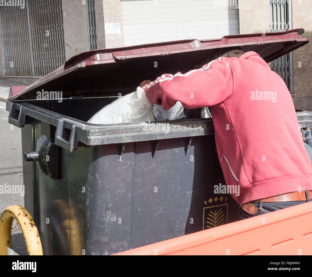 Homeless man rummaging  through household  rubbish container in Spain - Stock Image