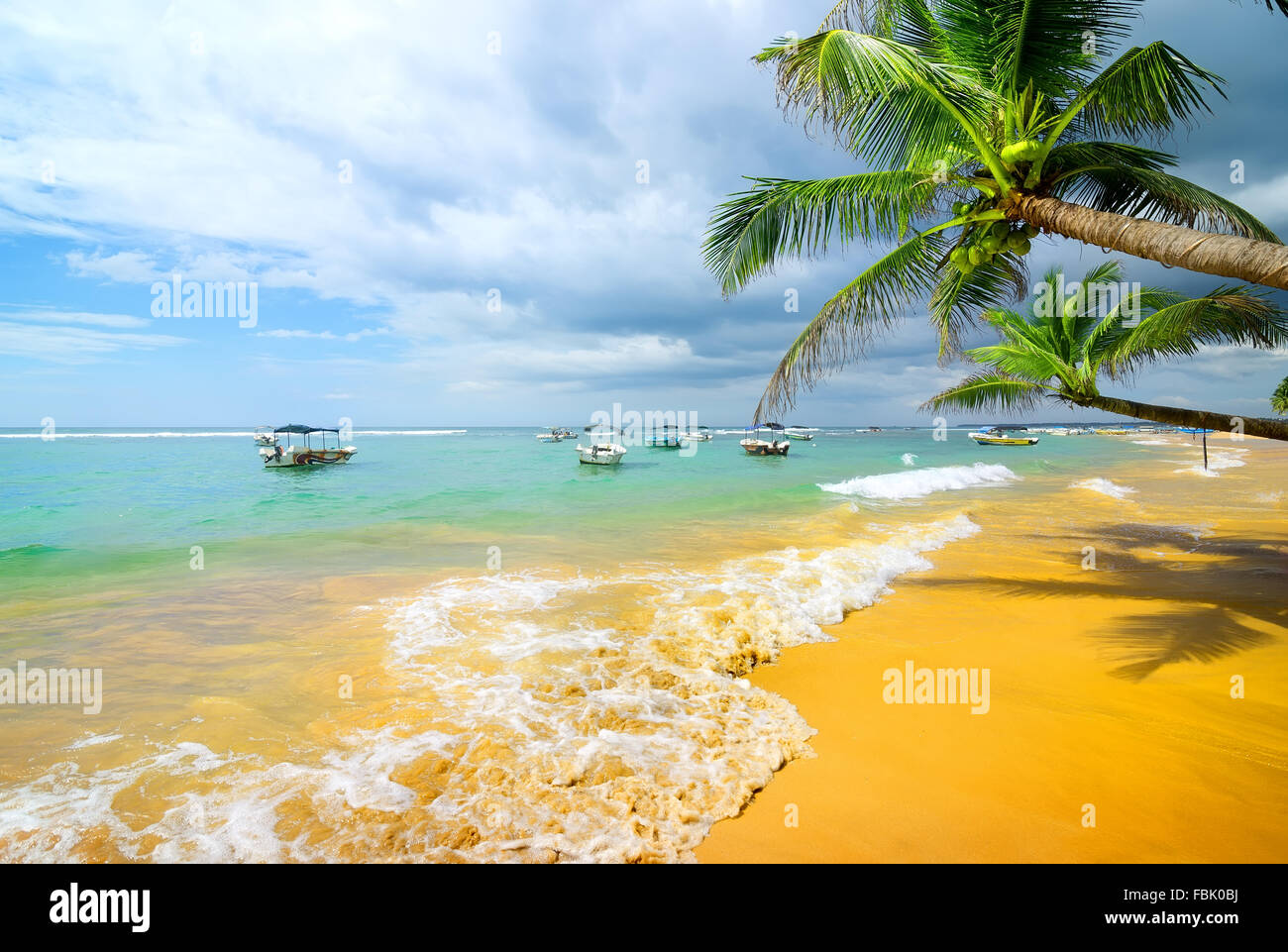 Boats in the ocean near sandy beach and palm trees - Stock Image