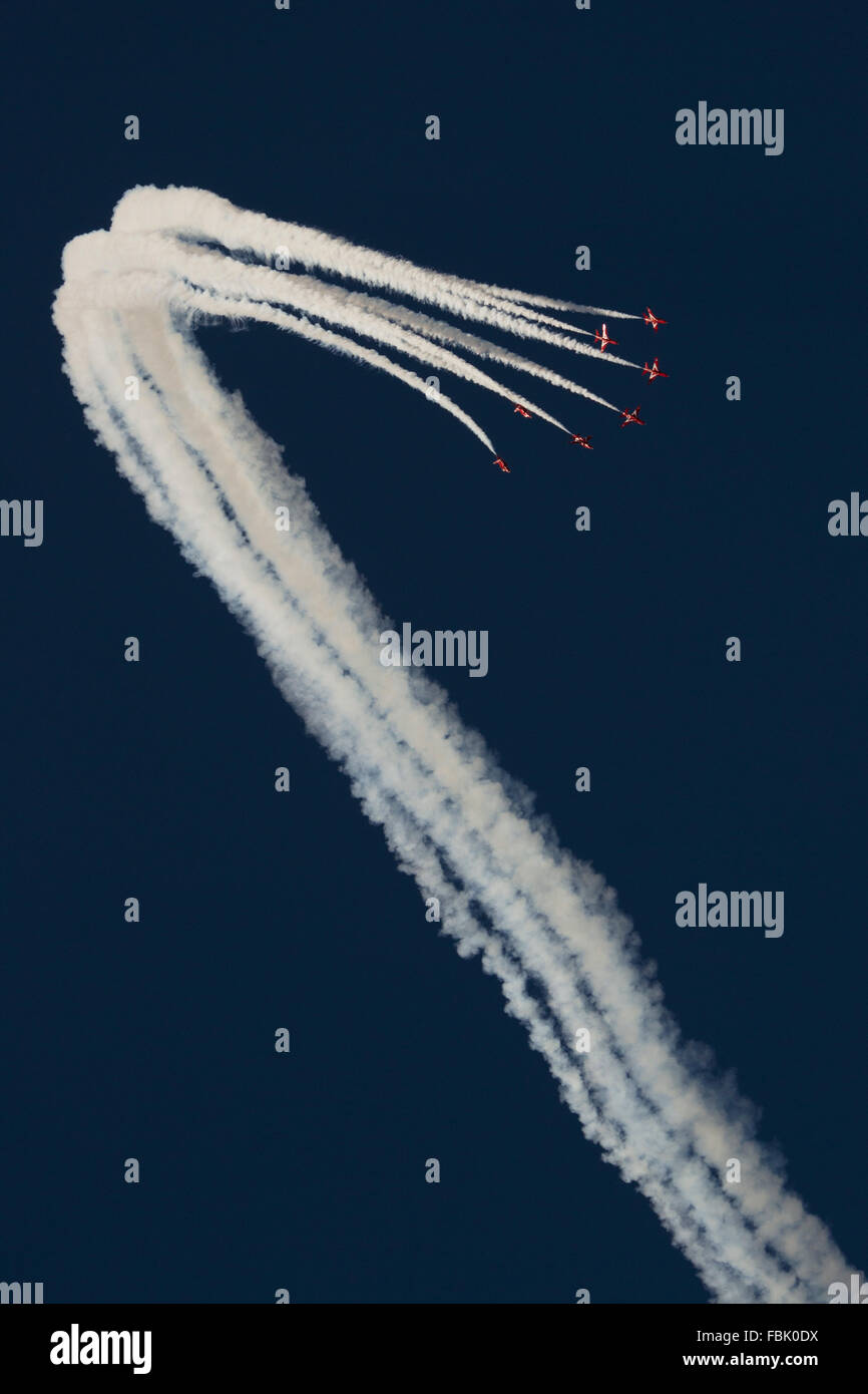 Red Arrows in formation against a vivid blue sky with white smoke at RIAT 2015 air show Stock Photo