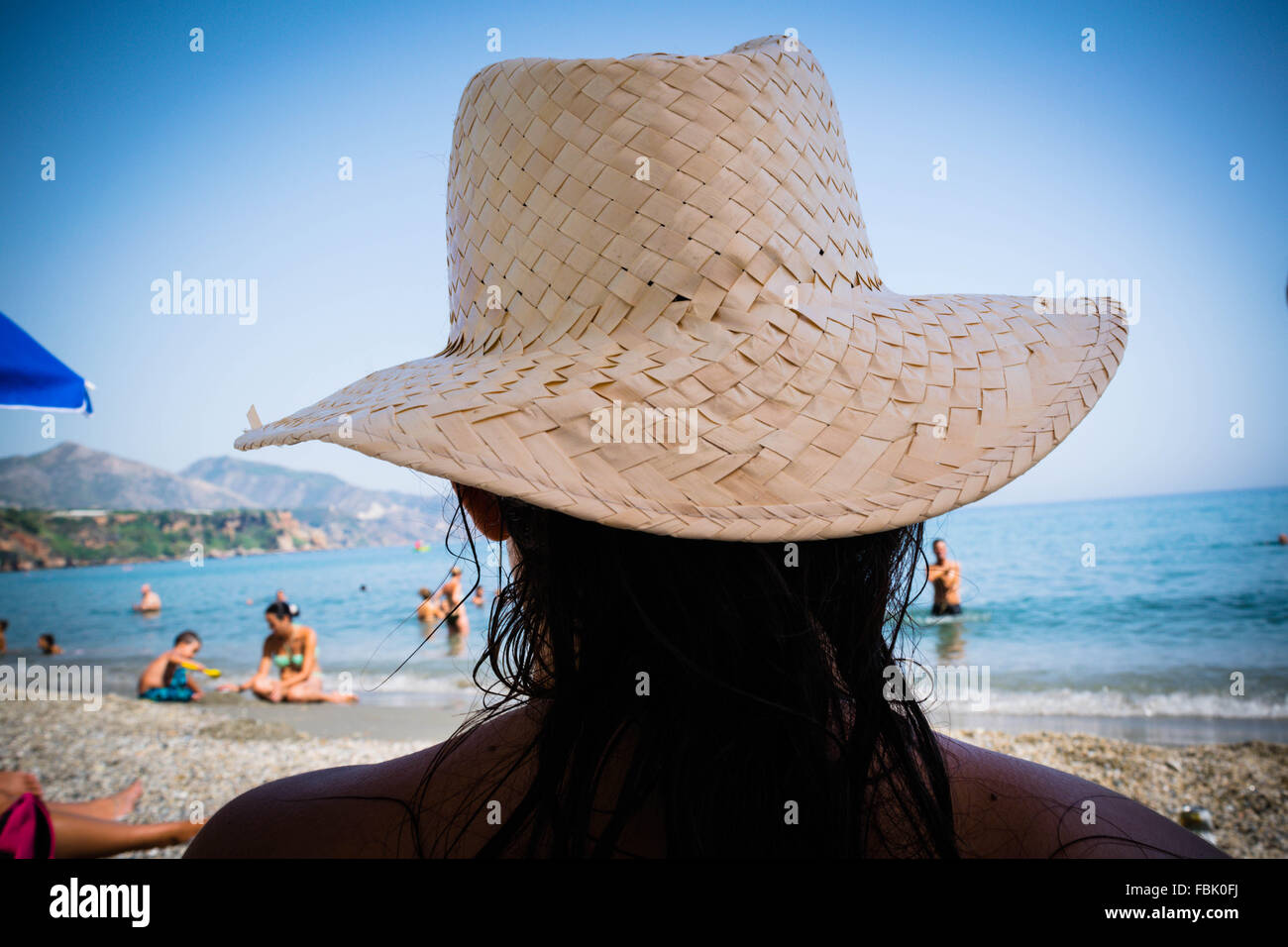 A holidaymaker relaxes on a Spanish beach wearing a straw hat. - Stock Image