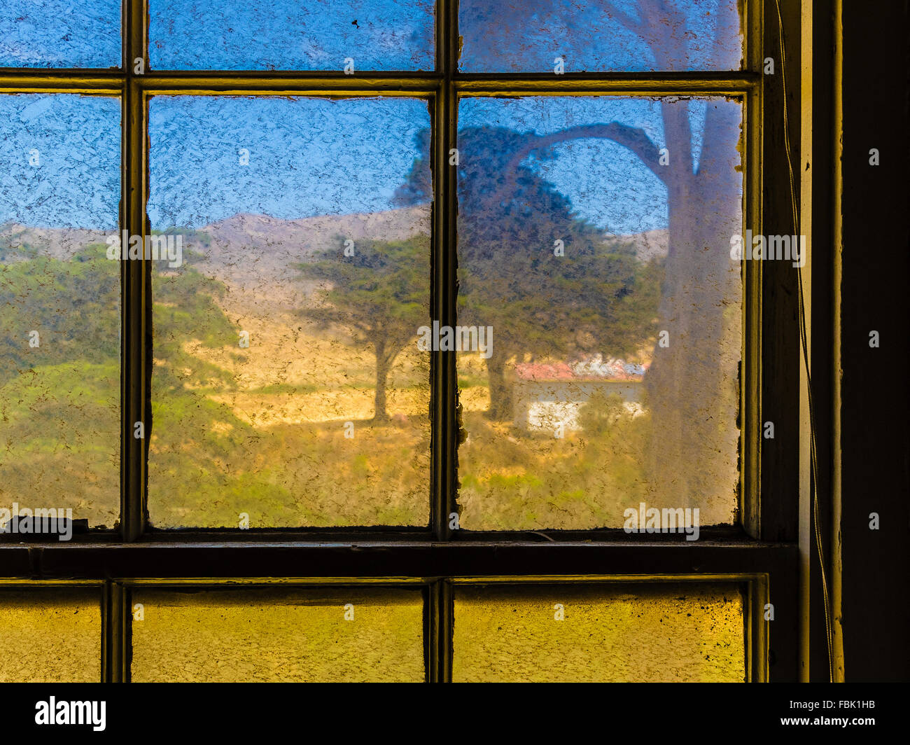 A landscape view of trees and hills looking out of dirty window panes. - Stock Image