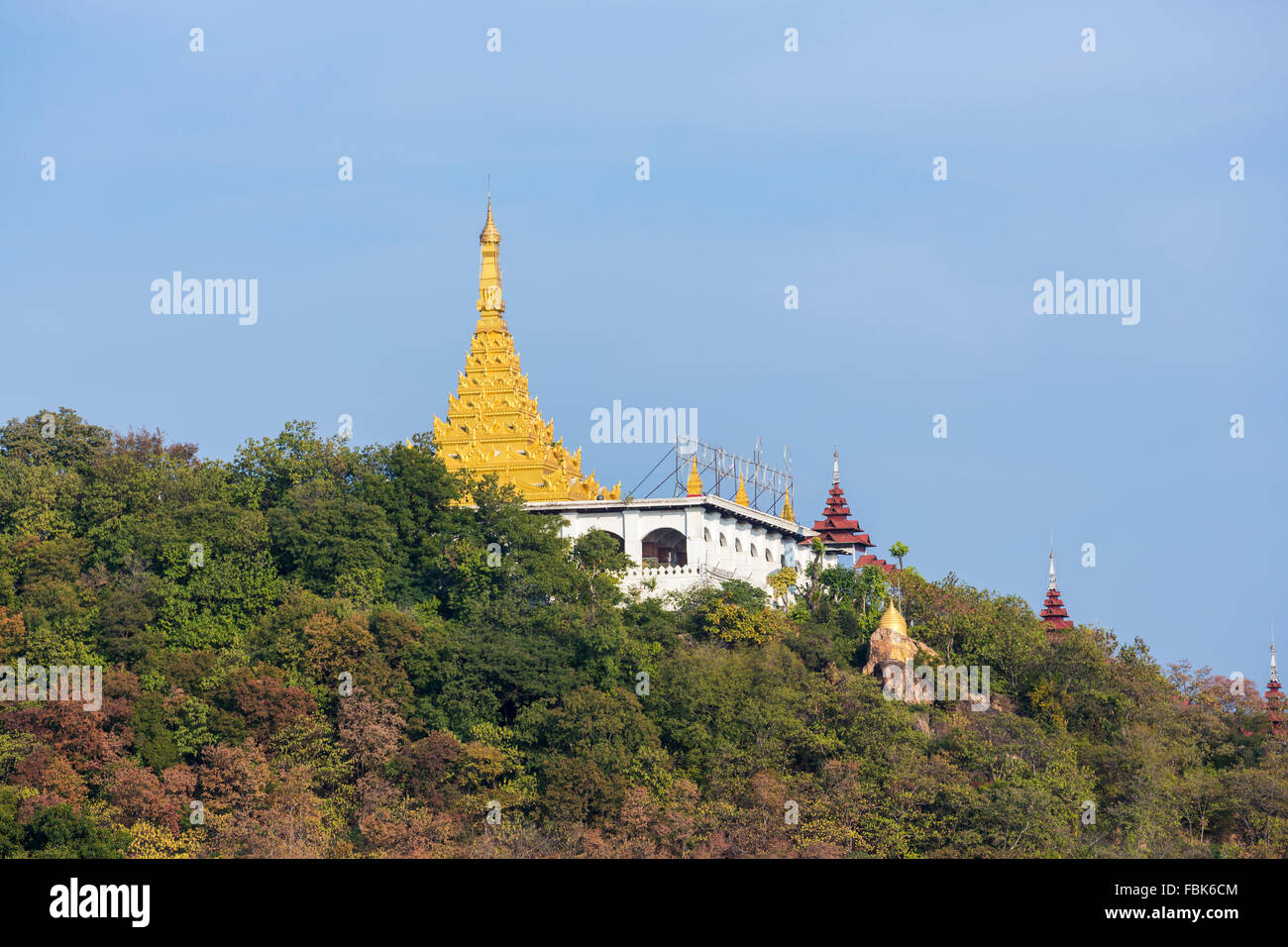 Typical gilded stupa of a shrine on the slopes of Mandalay Hill, Mandalay, Myanmar (Burma) under a clear blue sky - Stock Image
