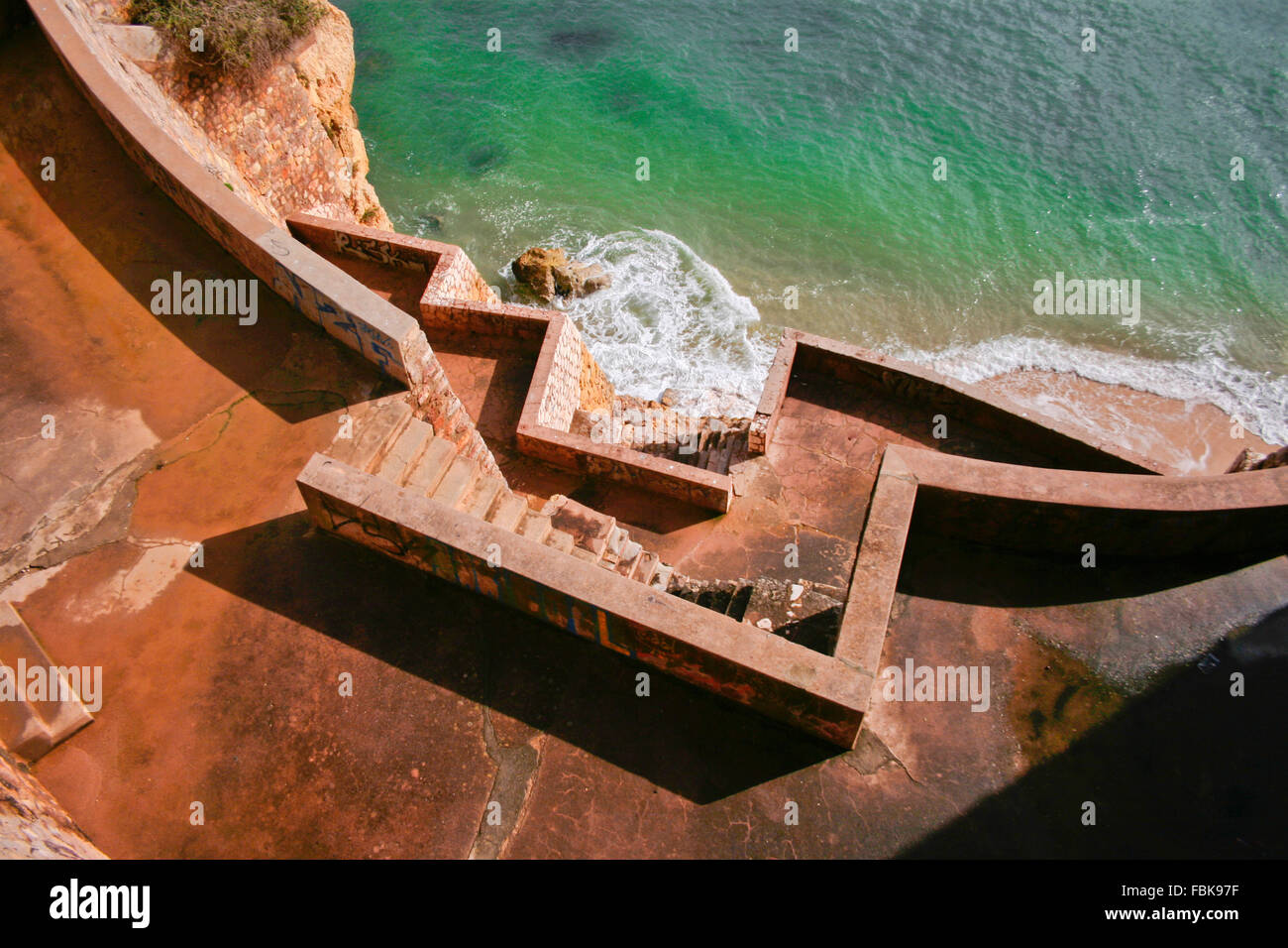 Concrete stairs going down until the seashore, Lagos, Portugal - Stock Image
