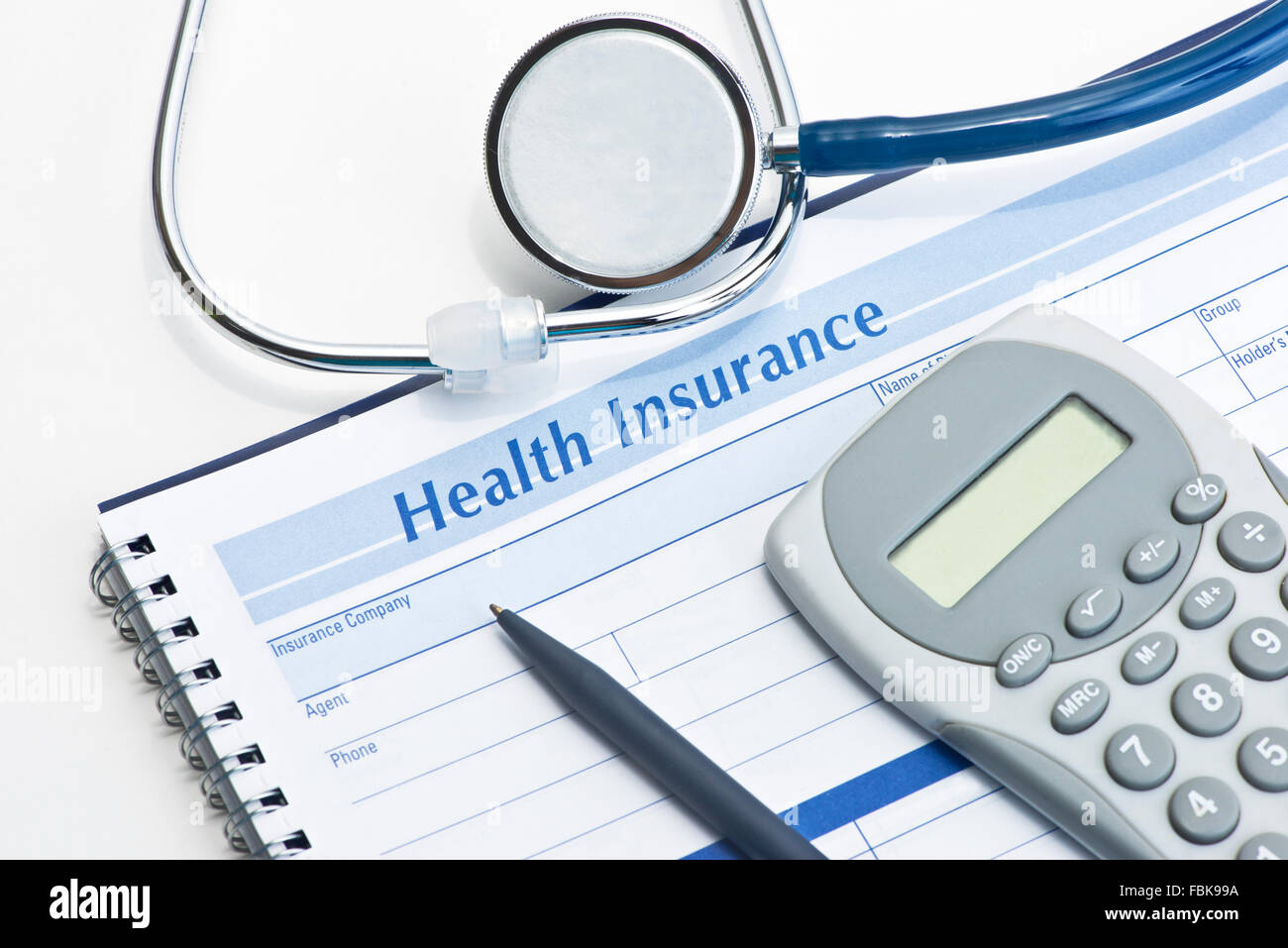 health insurance expense record with pen and calculator on white