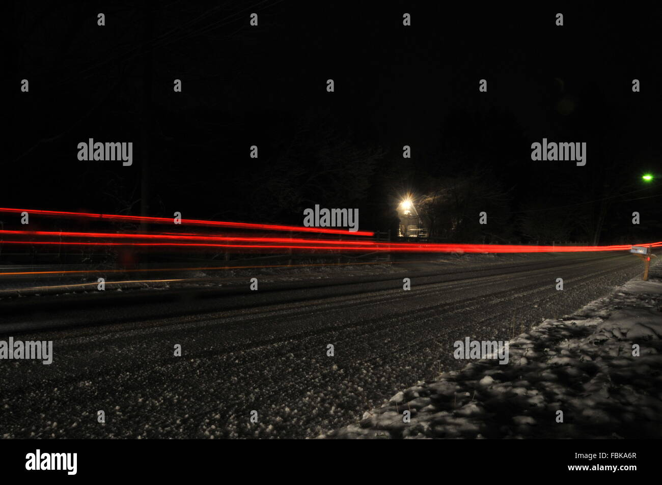 A wide angle shot of cars passing along a road on a corner allows for an interesting shot of a turning car - Stock Image