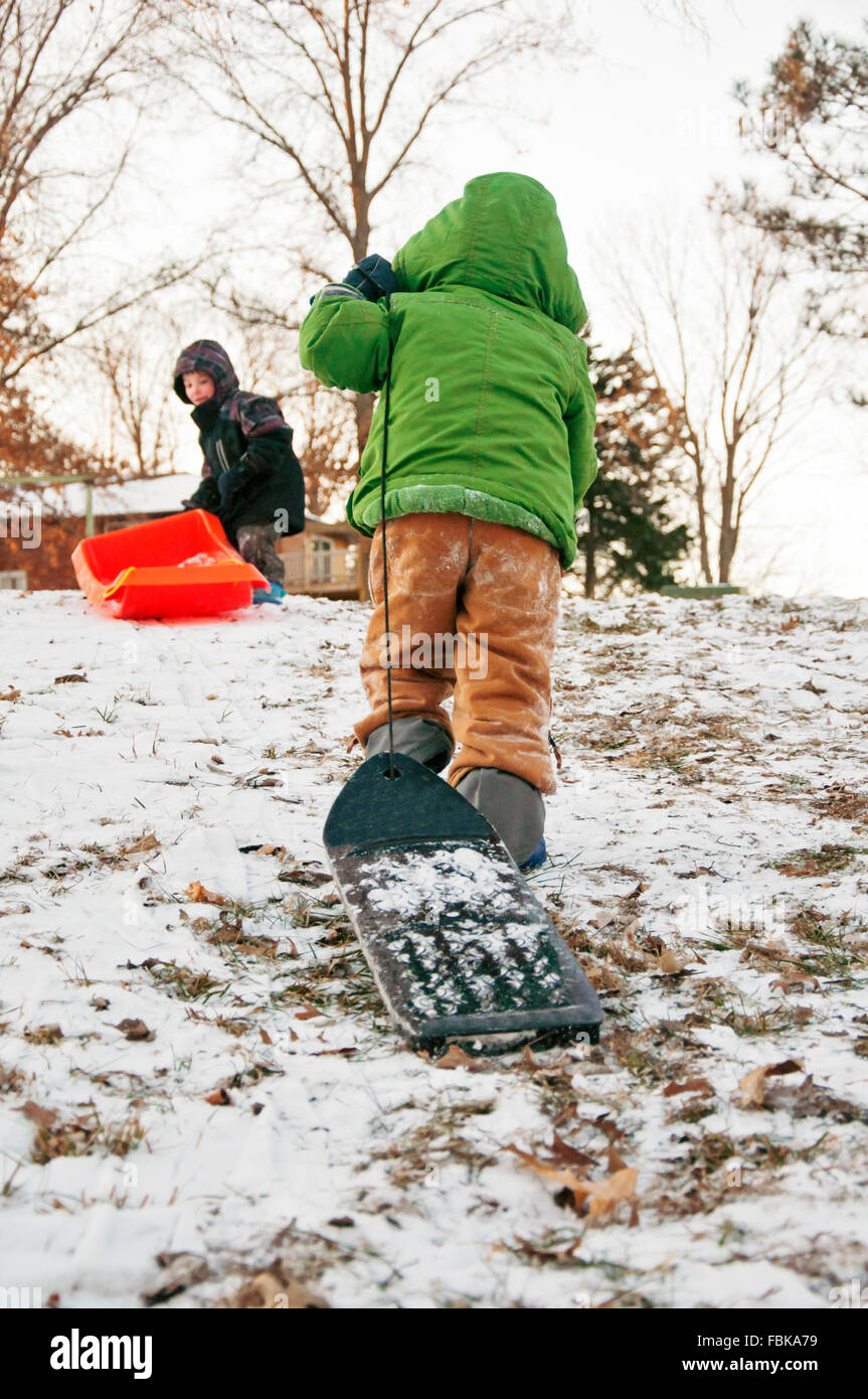 boy carrying sleds uphill - Stock Image
