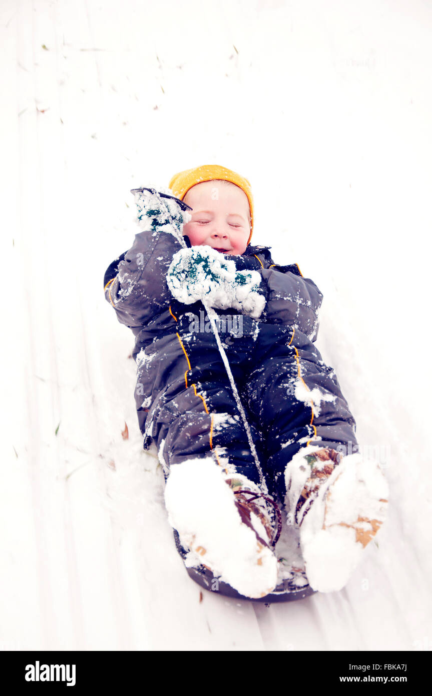 Little boy sledding downhill - Stock Image