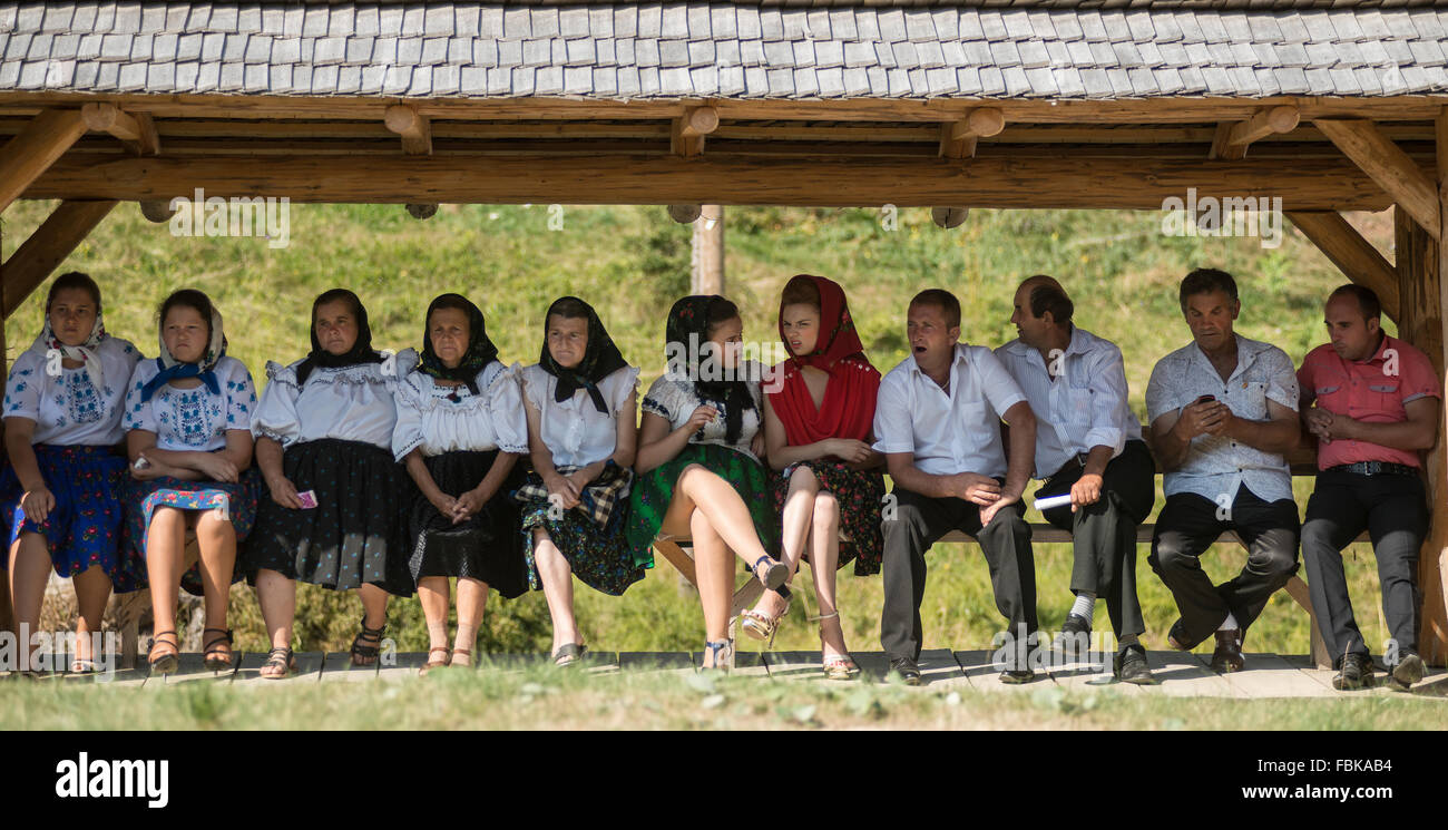women in traditional costume sitting in the shade of the district of Maramures, Romania - Stock Image