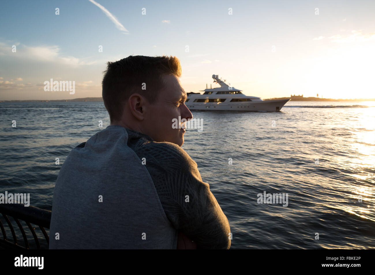 Adult man watching the sunset over a River as a private yacht sails past. - Stock Image