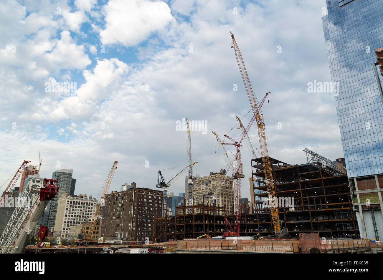 Multiple cranes and heavy lifting machinery on a construction site in Chelsea, New York City, as new skyscrapers Stock Photo