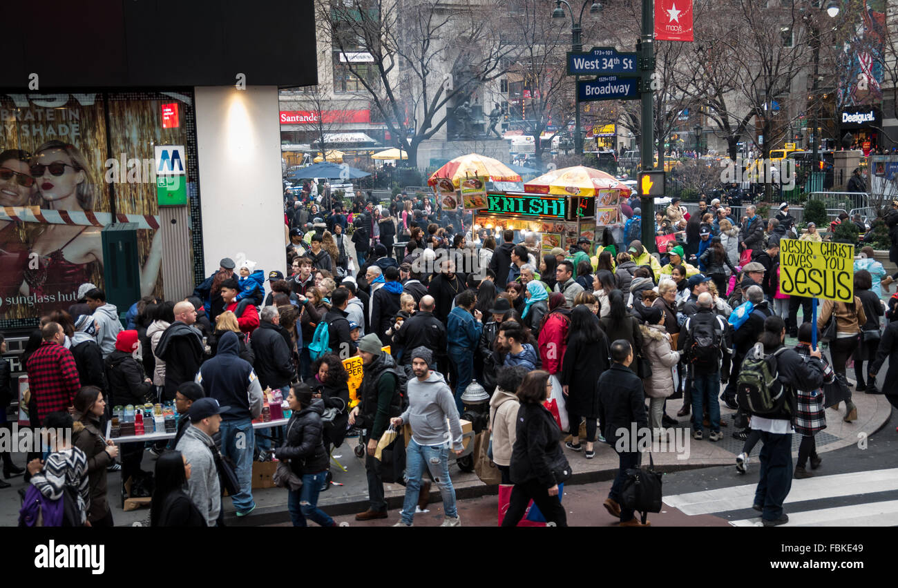 Huge crowd of people (shoppers and tourists) on 34th Street in New York City overspilling from the pavement into - Stock Image