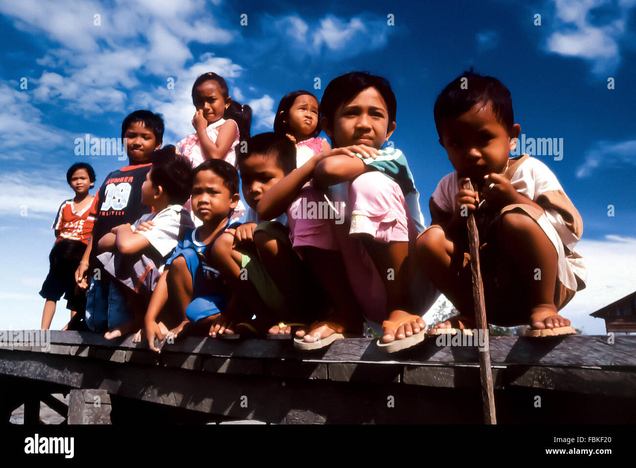 Asian children, grouping at a wooden jetty of a fishermen village in the Indonesian side of Borneo. - Stock Image