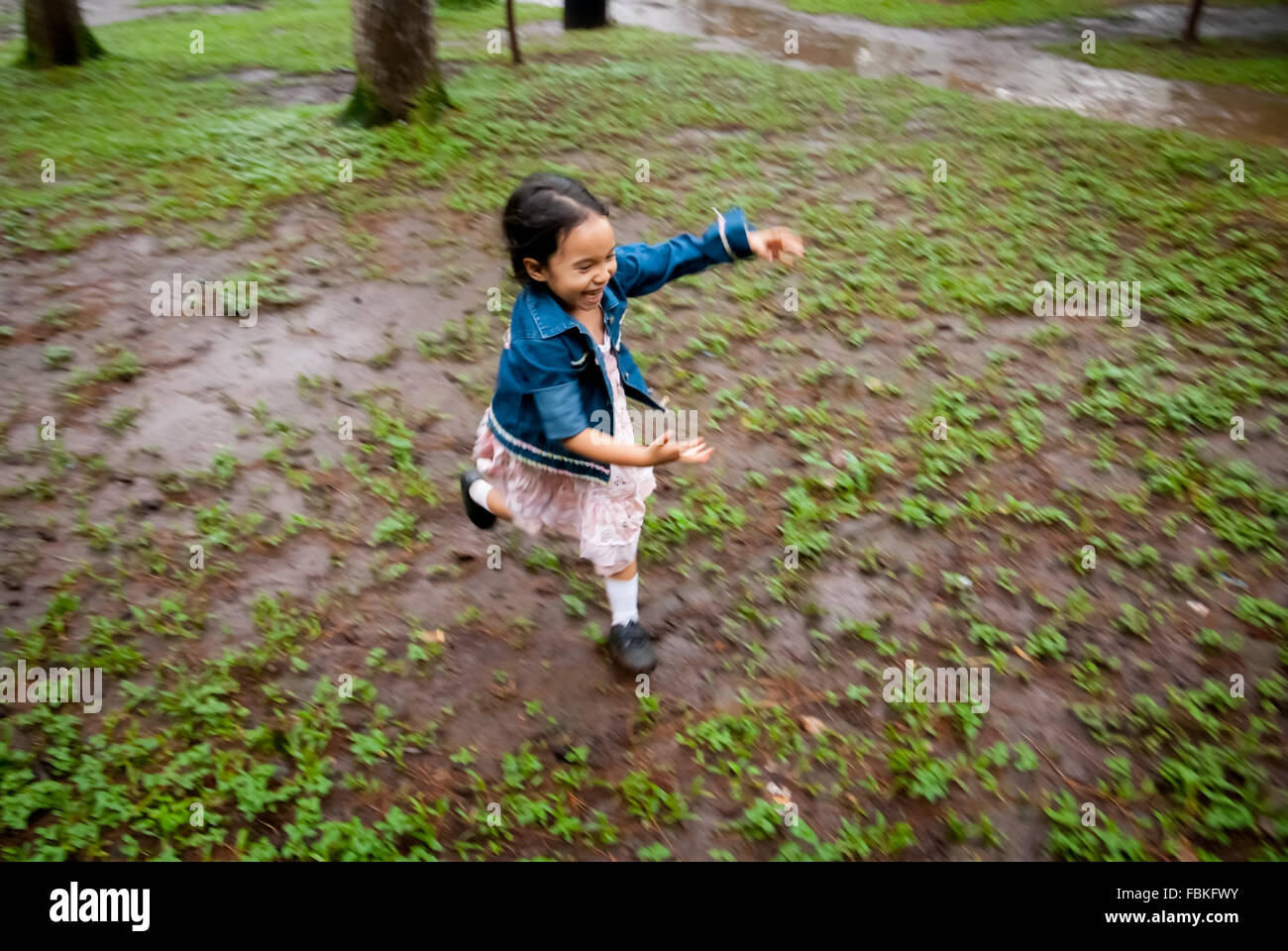 Little girl running happily in a muddy park after it had rained. - Stock Image