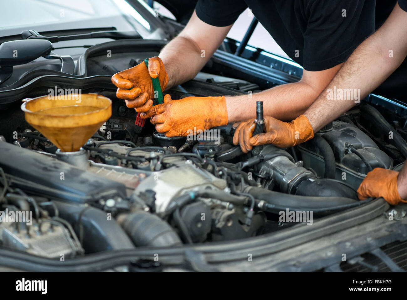Two mechanics working on a vehicle in a garage - Stock Image