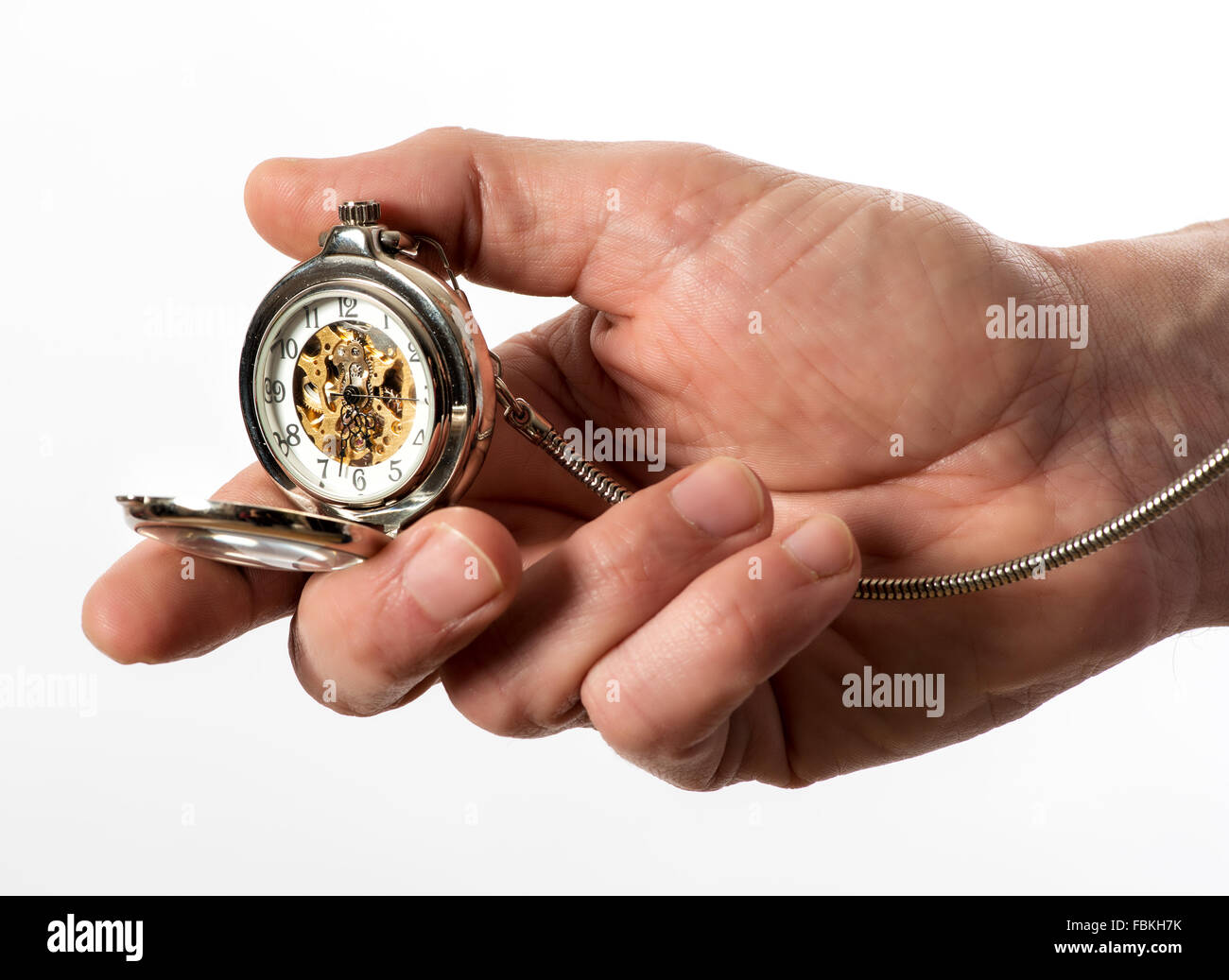 Man holding a vintage silver full hunter pocket watch in his hand opened to display the bronze mechanism through - Stock Image