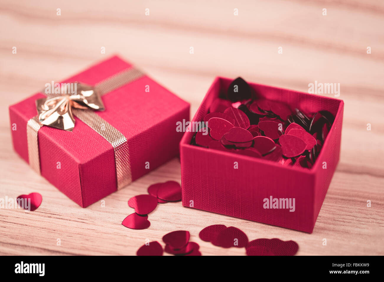 small red hearts confetti and present box on wooden background ...