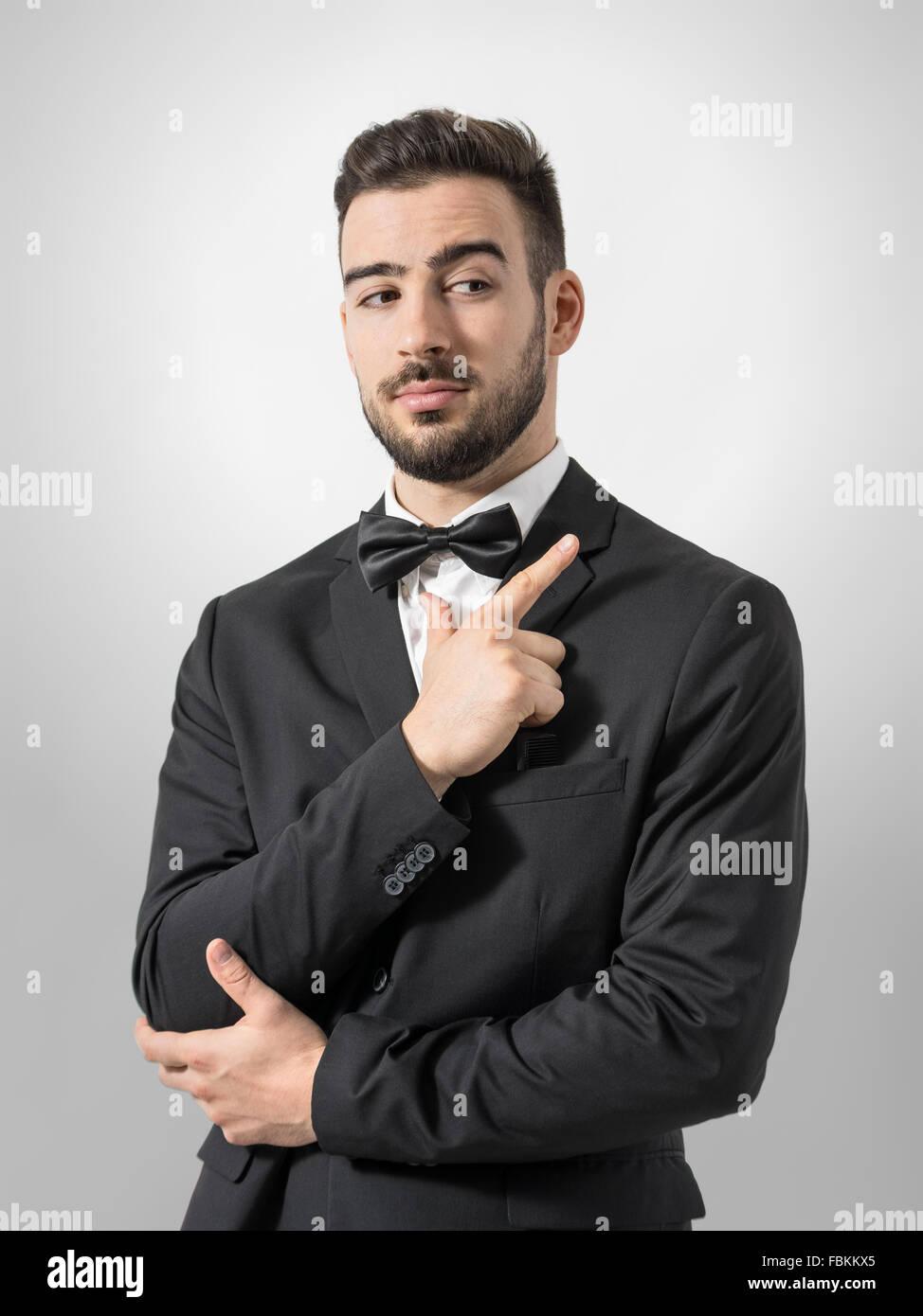 Secret service agent or bodyguard mimic pistol with hand gun gesture sign. Desaturated portrait over gray studio - Stock Image