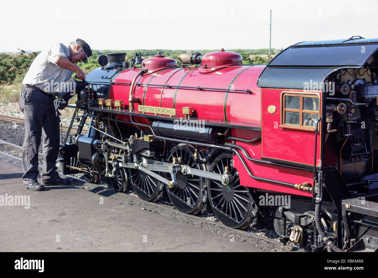 England, Kent, Dungeness. The driver tops up the oil levels in the miniature steam locomotive, 'Winston Churchill'. Stock Photo