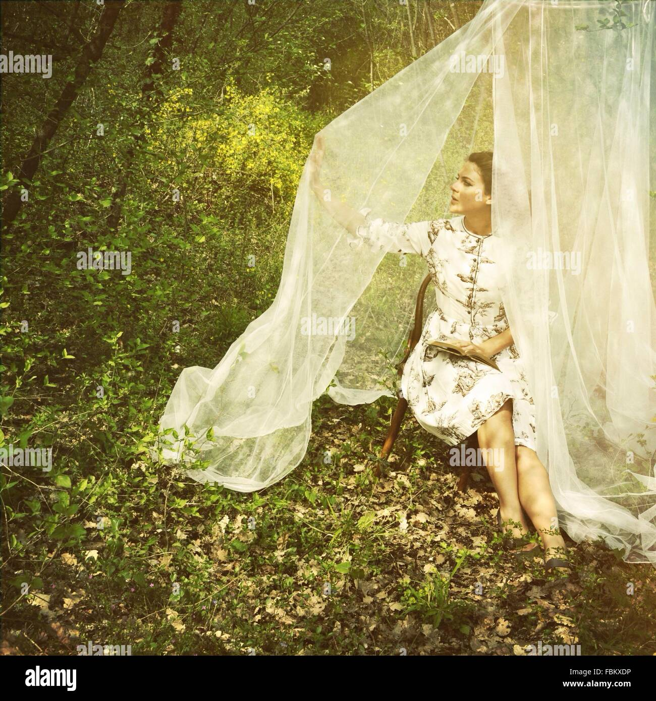 Woman With Book Touching Curtain While Sitting On Chair At Forest - Stock Image