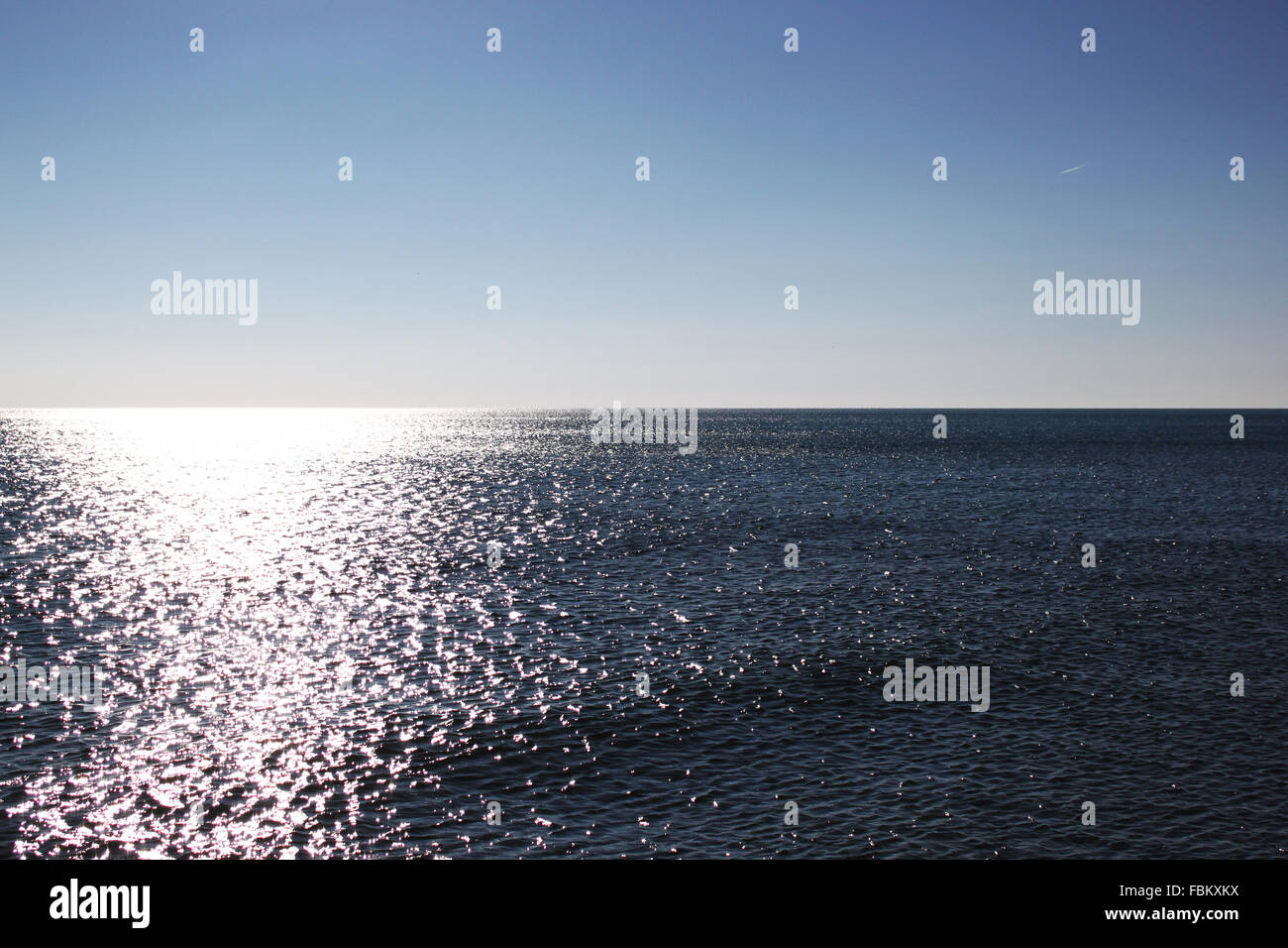 View on the quietly ocean in Narbonne/ France under a cloud-free sky - Stock Image