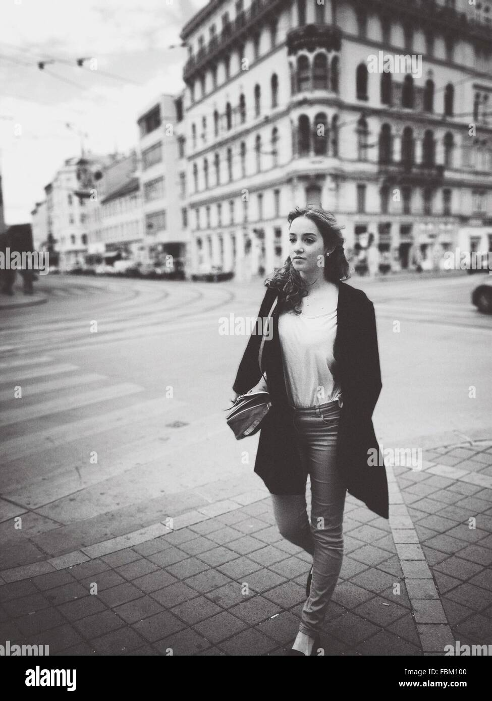 Full Length Of Young Woman Walking On City Street - Stock Image
