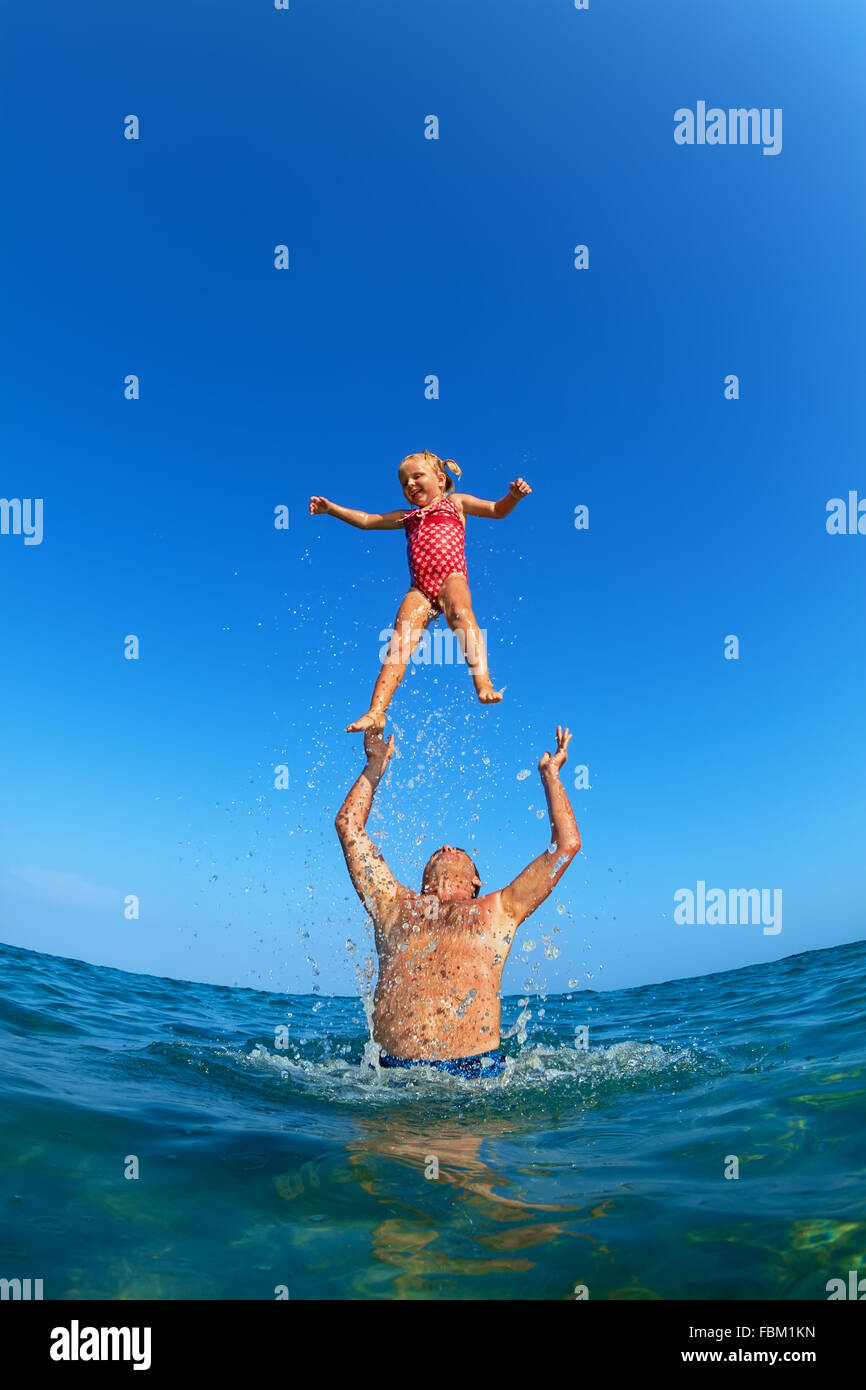 Grandfather tossing up the high air with water splashes joyful baby girl on sea beach. Outdoors child activity, - Stock Image