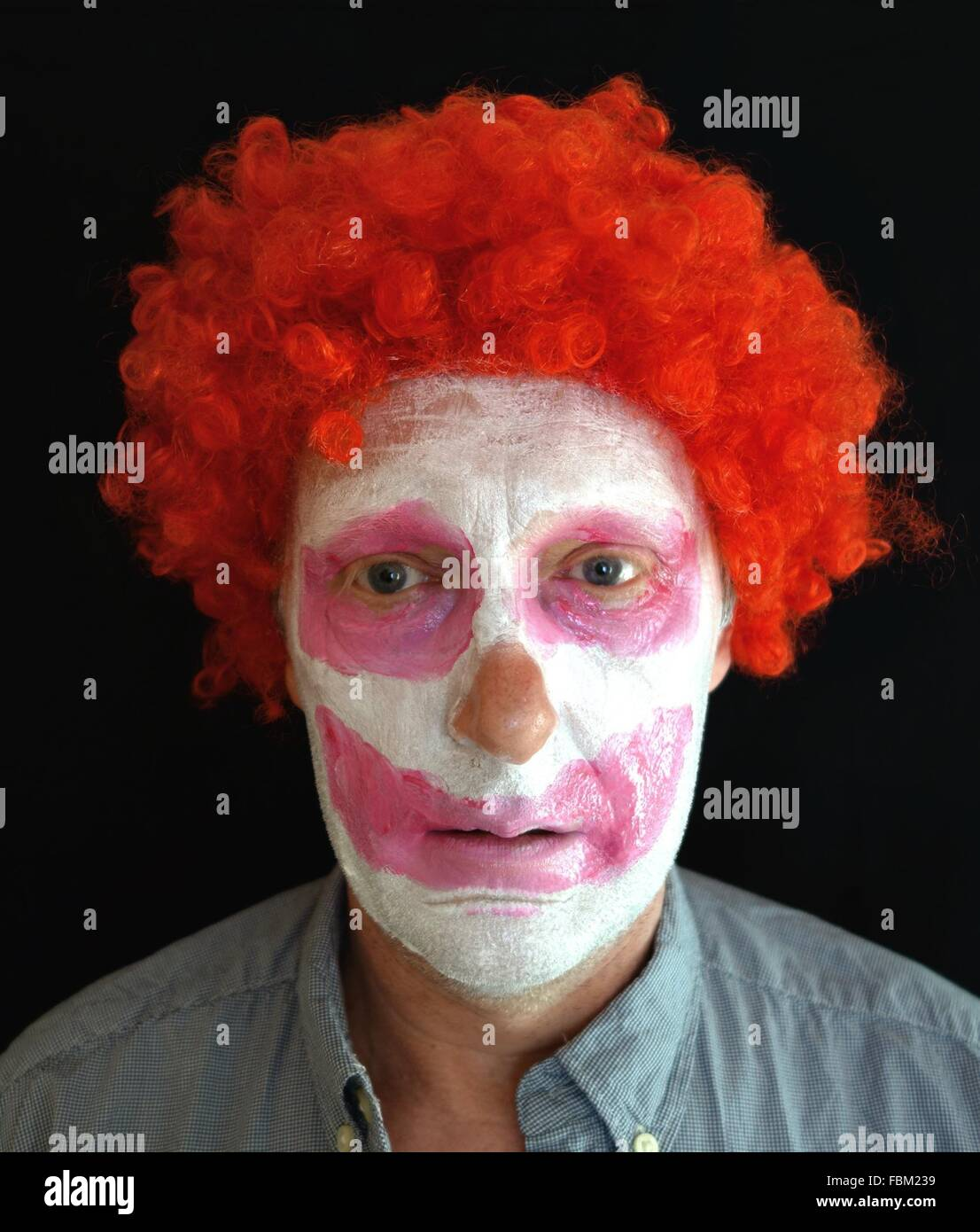 Close-Up Portrait Of A Young Man With Face Paint And Red Wig - Stock Image