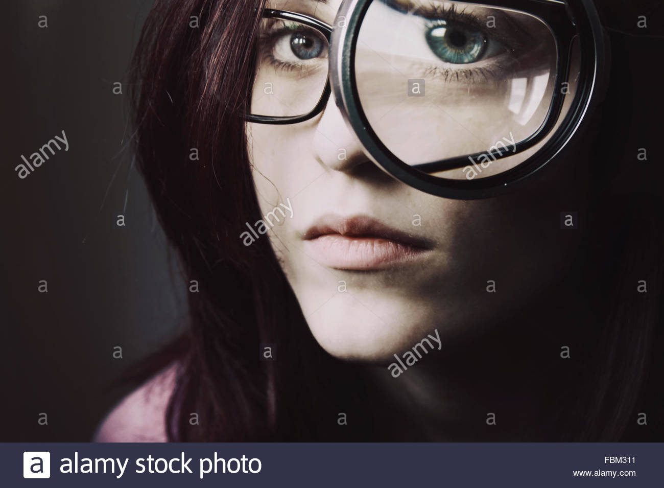 Woman Looking Through Magnifying Glass - Stock Image