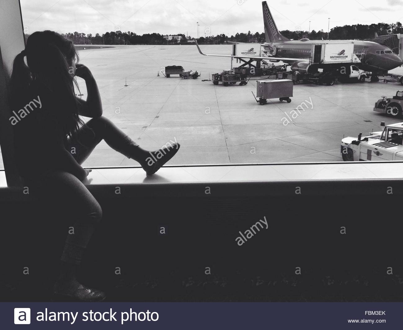 Little Girl Sitting On Window Sill At Airport - Stock Image