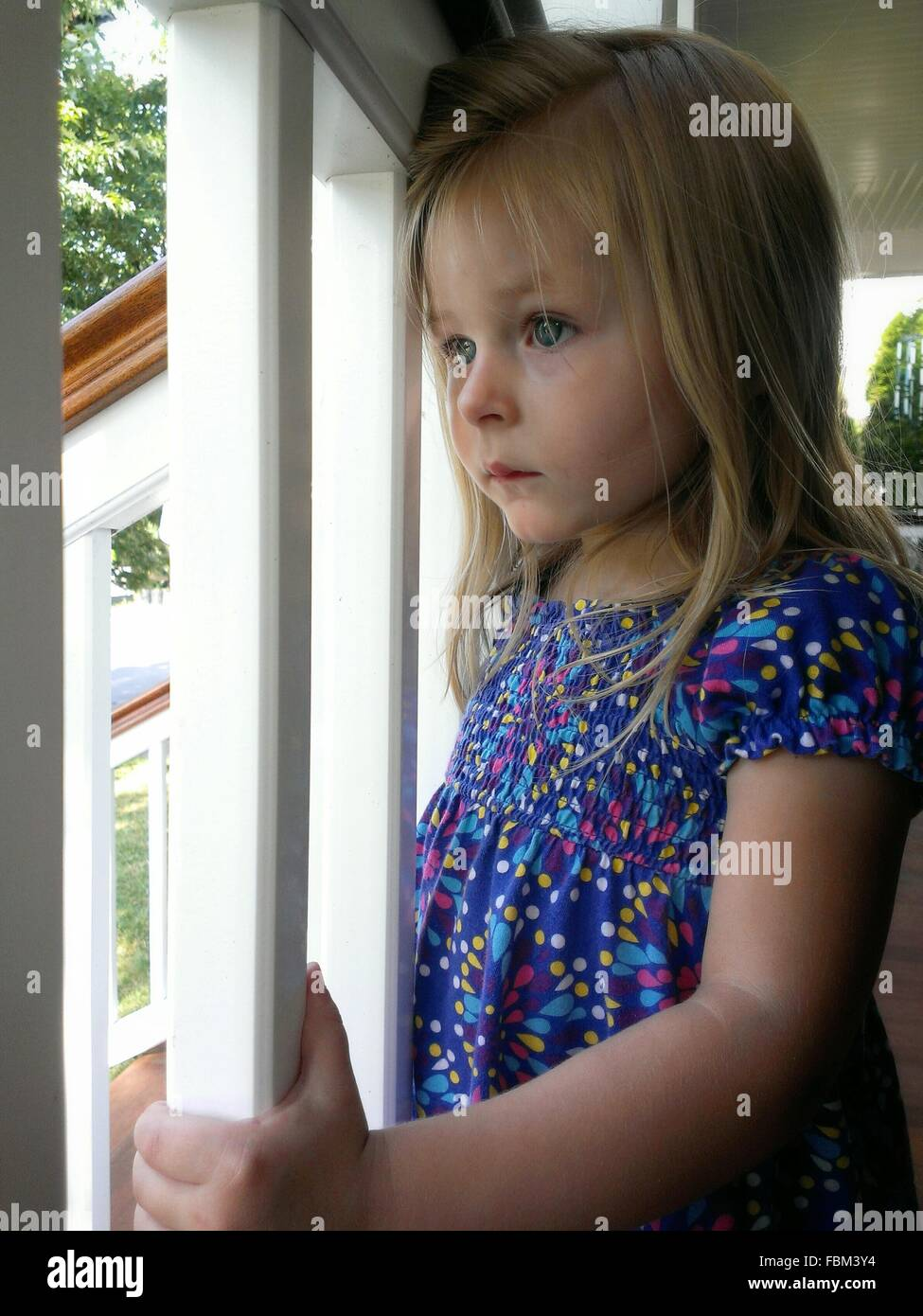 Close-Up Of A Cute Girl Looking Through Window - Stock Image