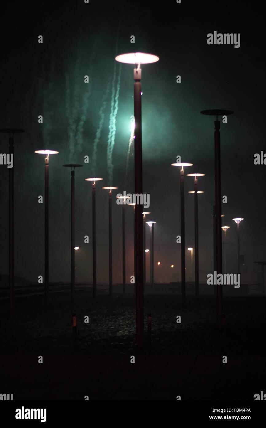 Illuminated Street Lights Against Firework In Sky At Night Stock Photo