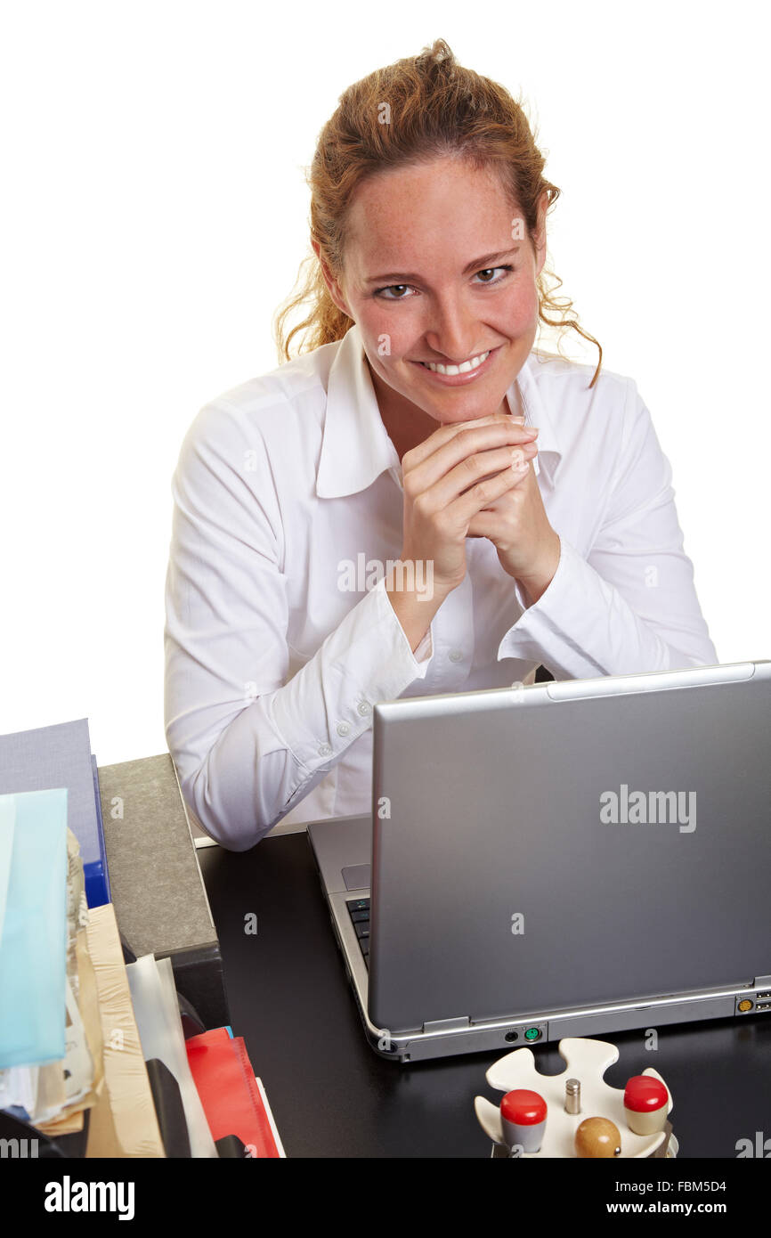 Smiling business woman sitting at laptop behind her desk Stock Photo