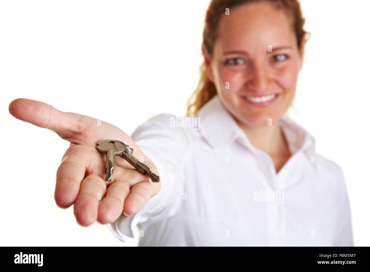 Business woman offering two keys on her open palm - Stock Image