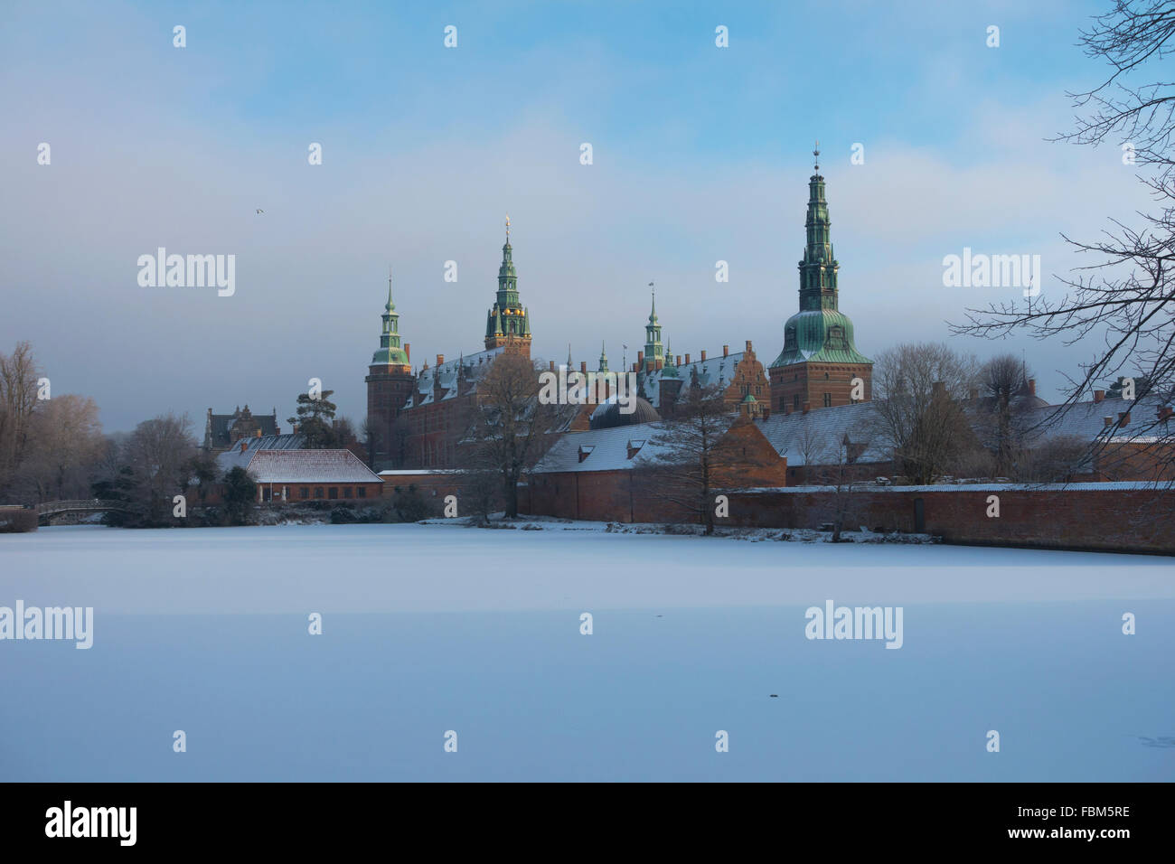 Frederiksborg Castle on a winter's day. Snow on frozen castle lake. The sun is breaking through the frosty mist. - Stock Image