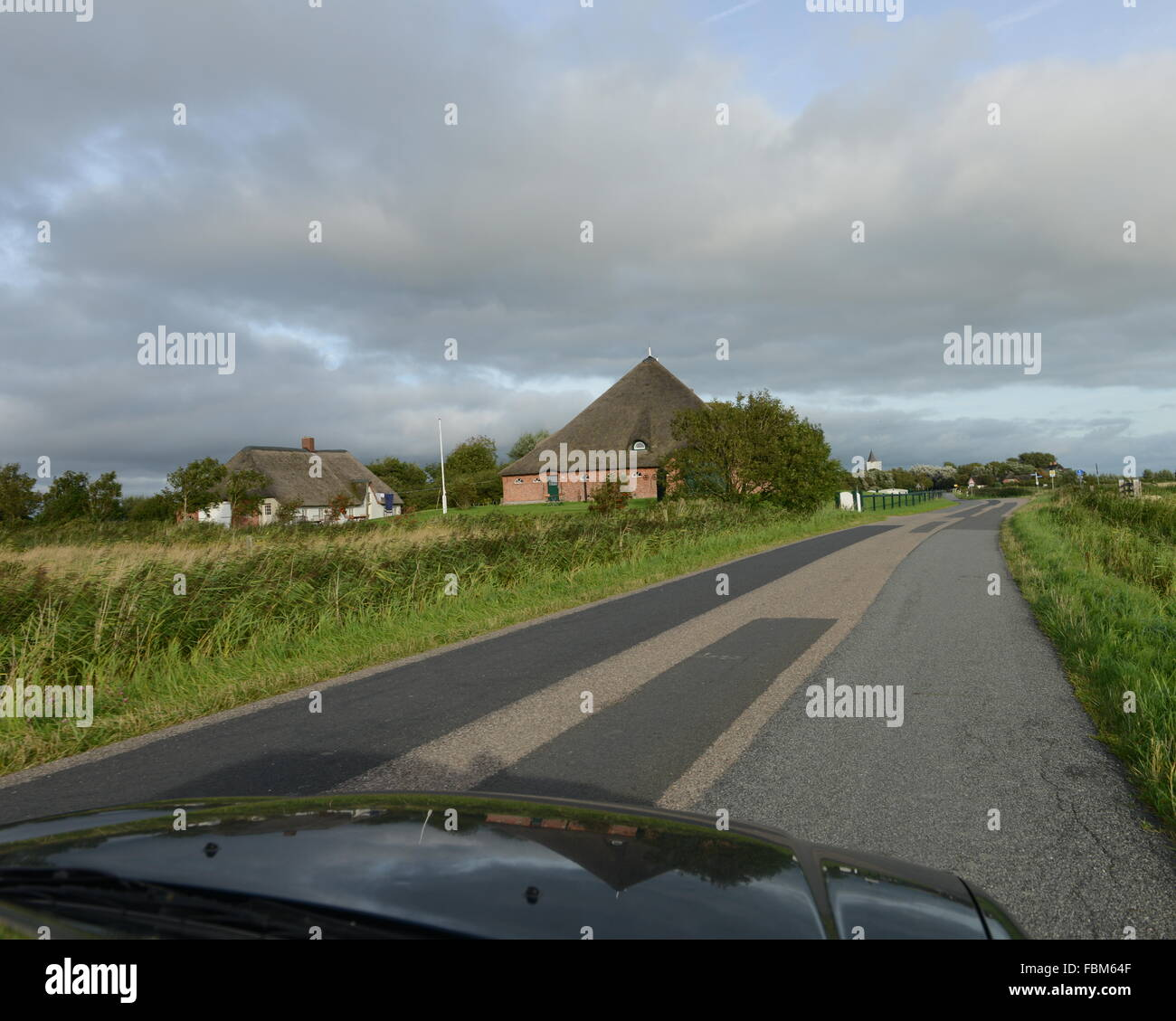 Cropped Image Of Car On Country Road By Houses Against Cloudy Sky - Stock Image