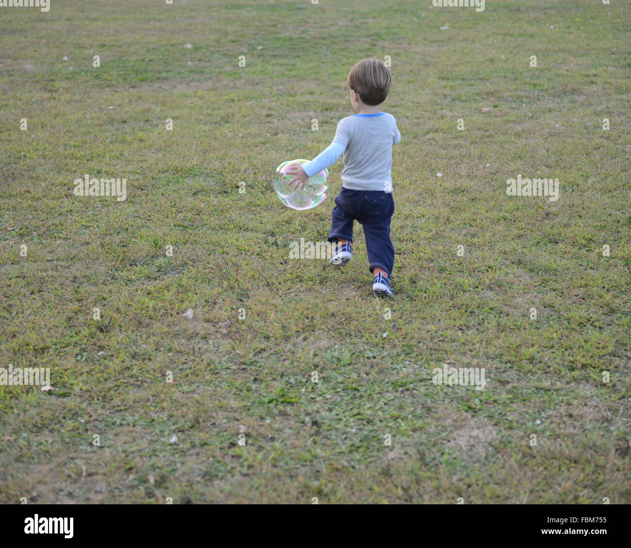 Boy Running With Soap Suds Bubble - Stock Image