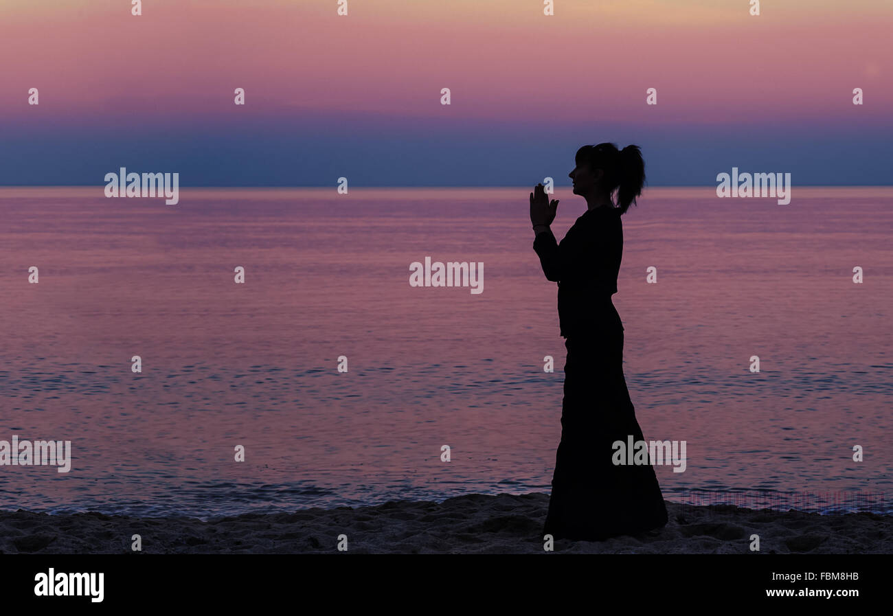Silhouette of a woman standing on beach with hands in prayer position - Stock Image