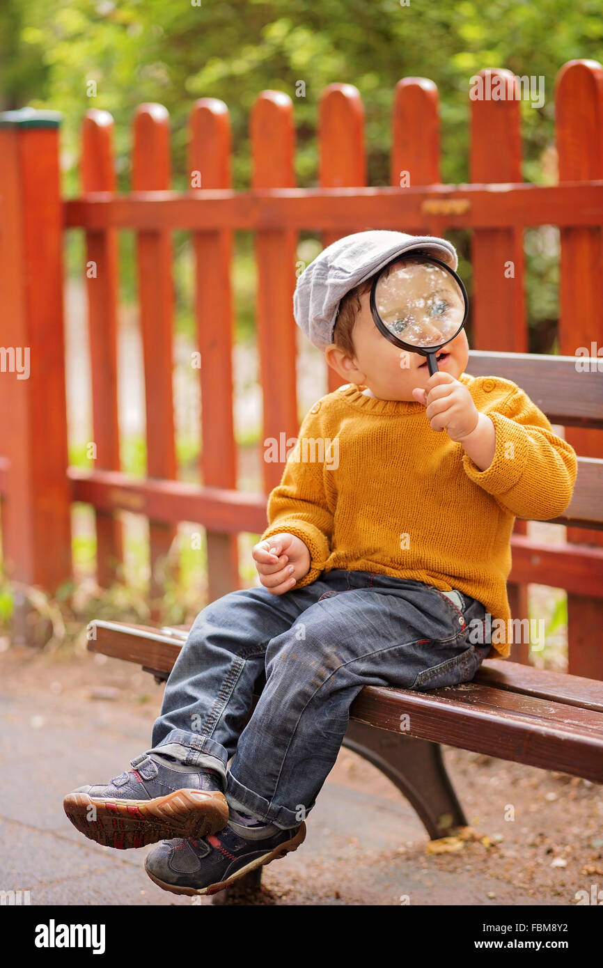 Boy sitting on bench holding a magnifying glass - Stock Image