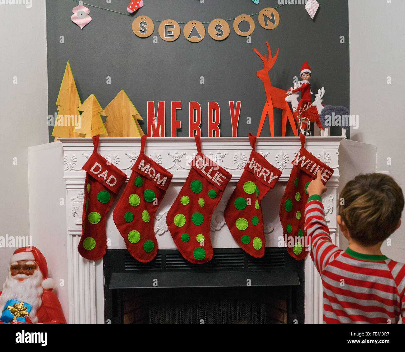 Boy Standing In Front Of Fireplace Pointing At Christmas Stockings