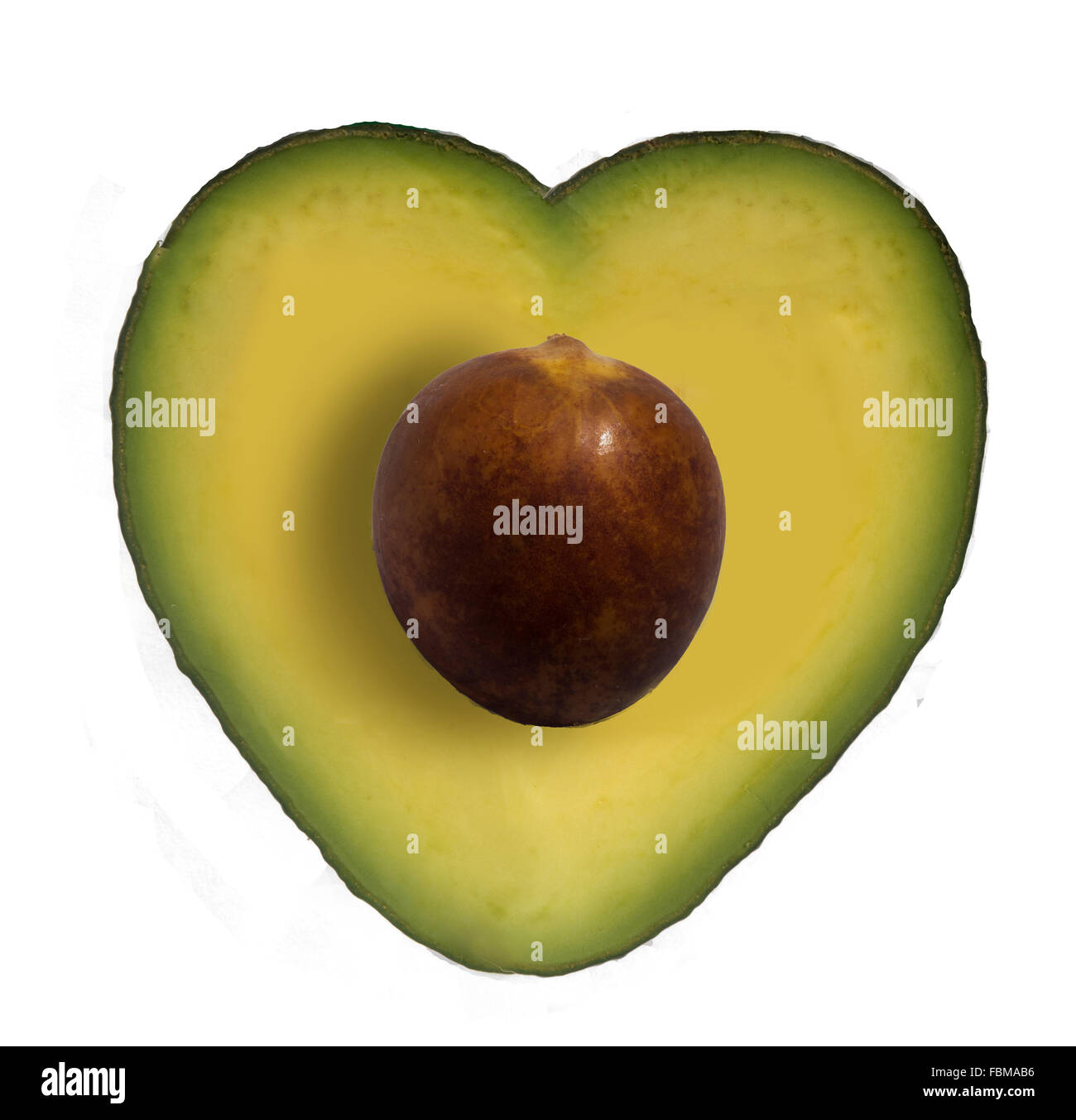 Close-Up Of Avocado Cut In Heart Shape Against White Background - Stock Image