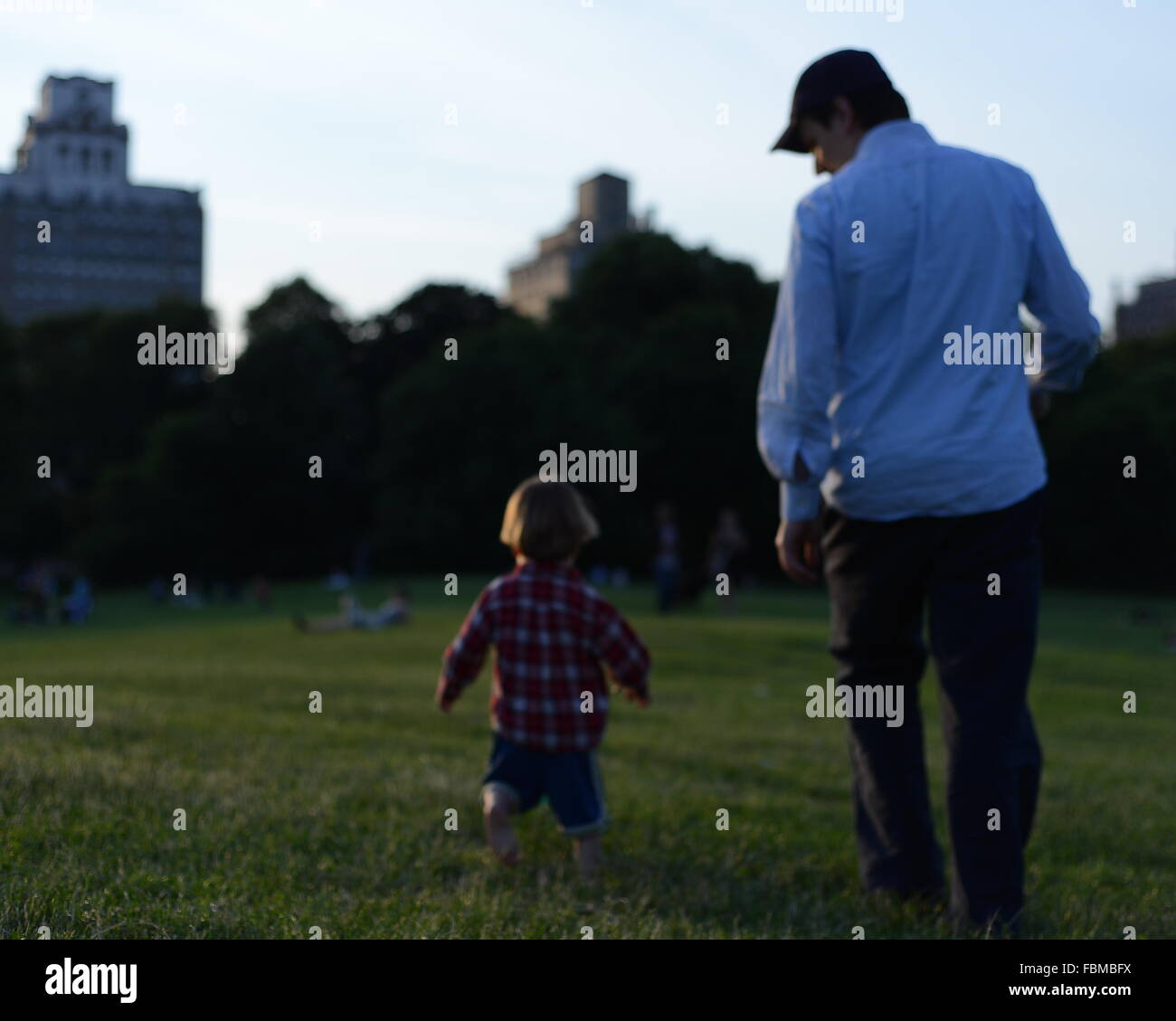 Rear View Of Father And Son Walking On Landscape - Stock Image