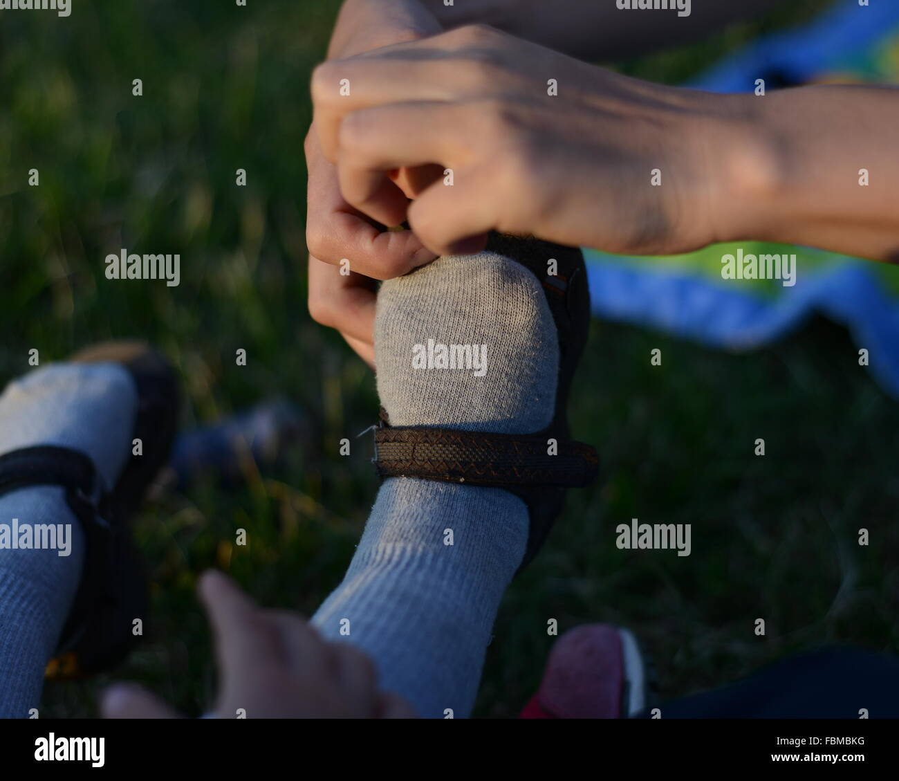 Close-Up Of Hands Helping Kid With Footwear - Stock Image