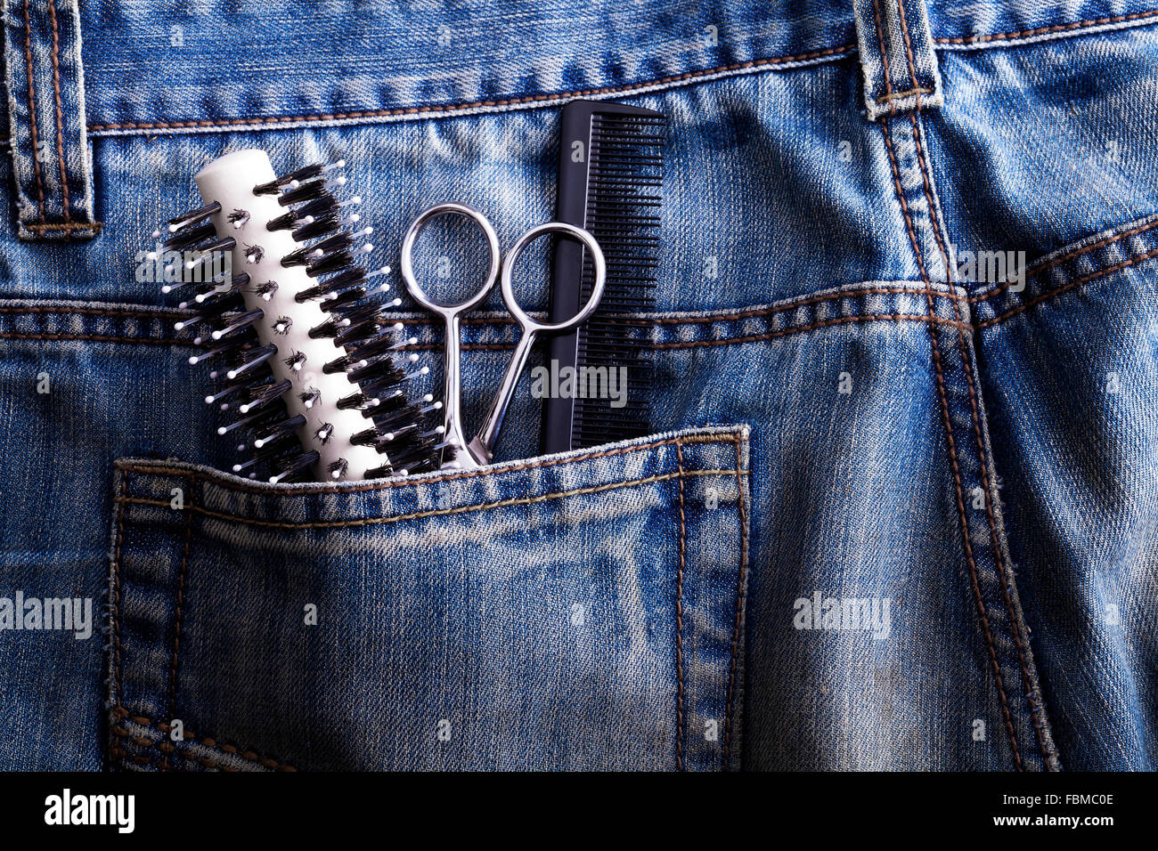 Brush, scissors and comb in the pocket of jeans - Stock Image