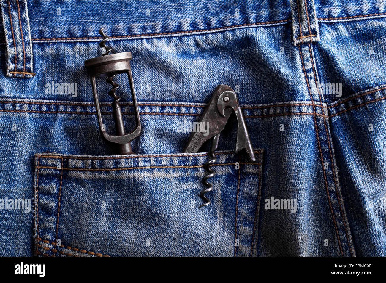 Old corkscrew, bottle opener in the pocket of jeans - Stock Image