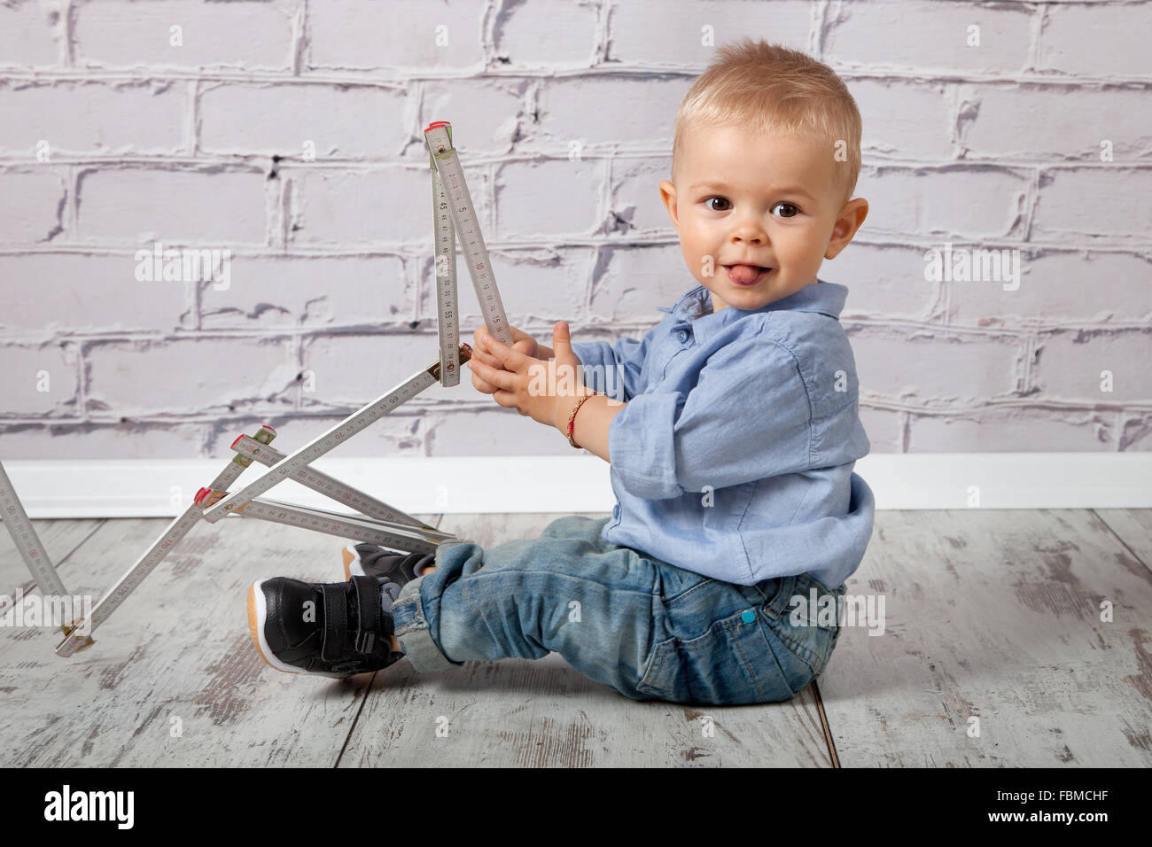 Child playing with wooden meter stick - Stock Image