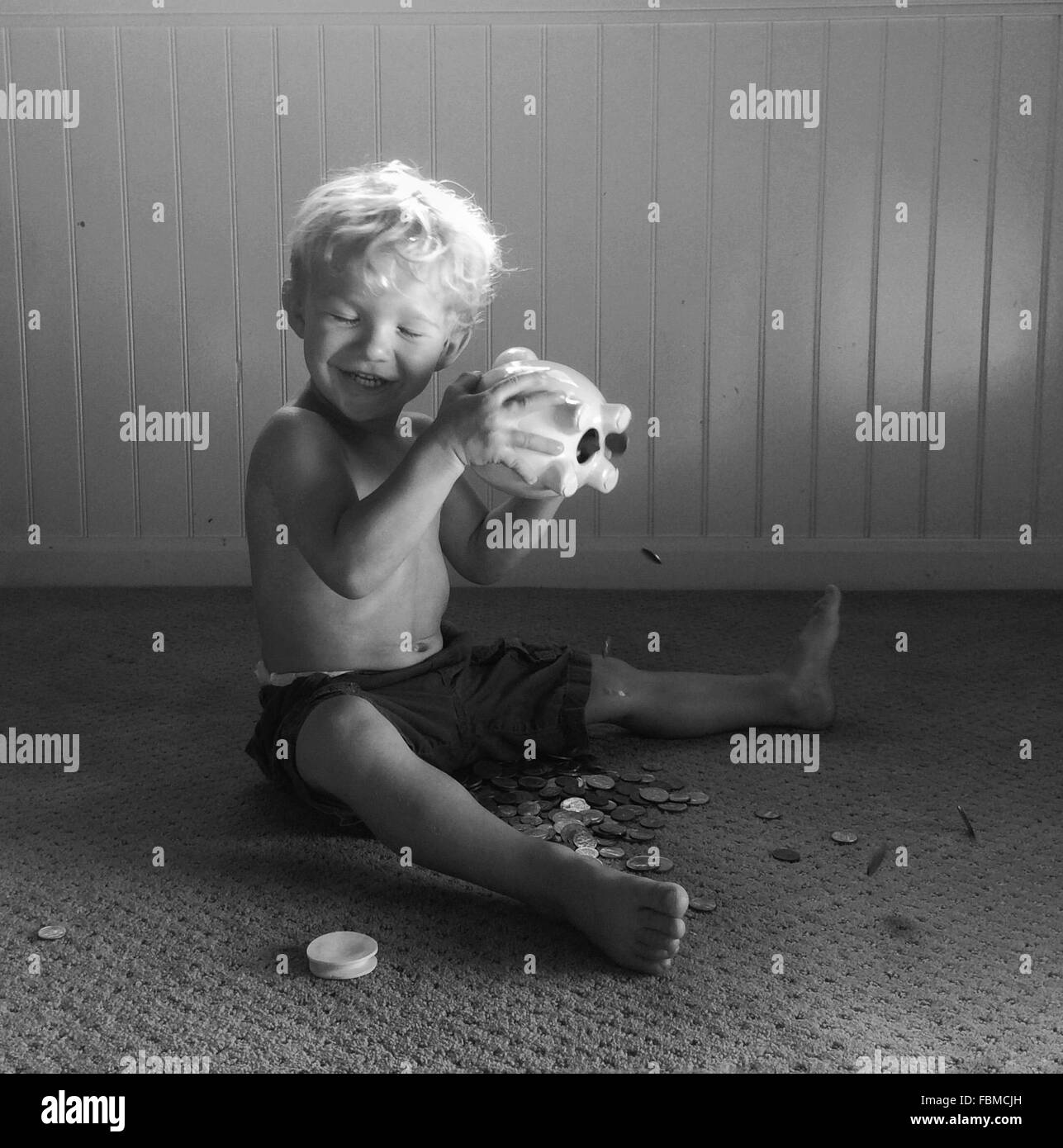 Boy shaking a piggy bank - Stock Image